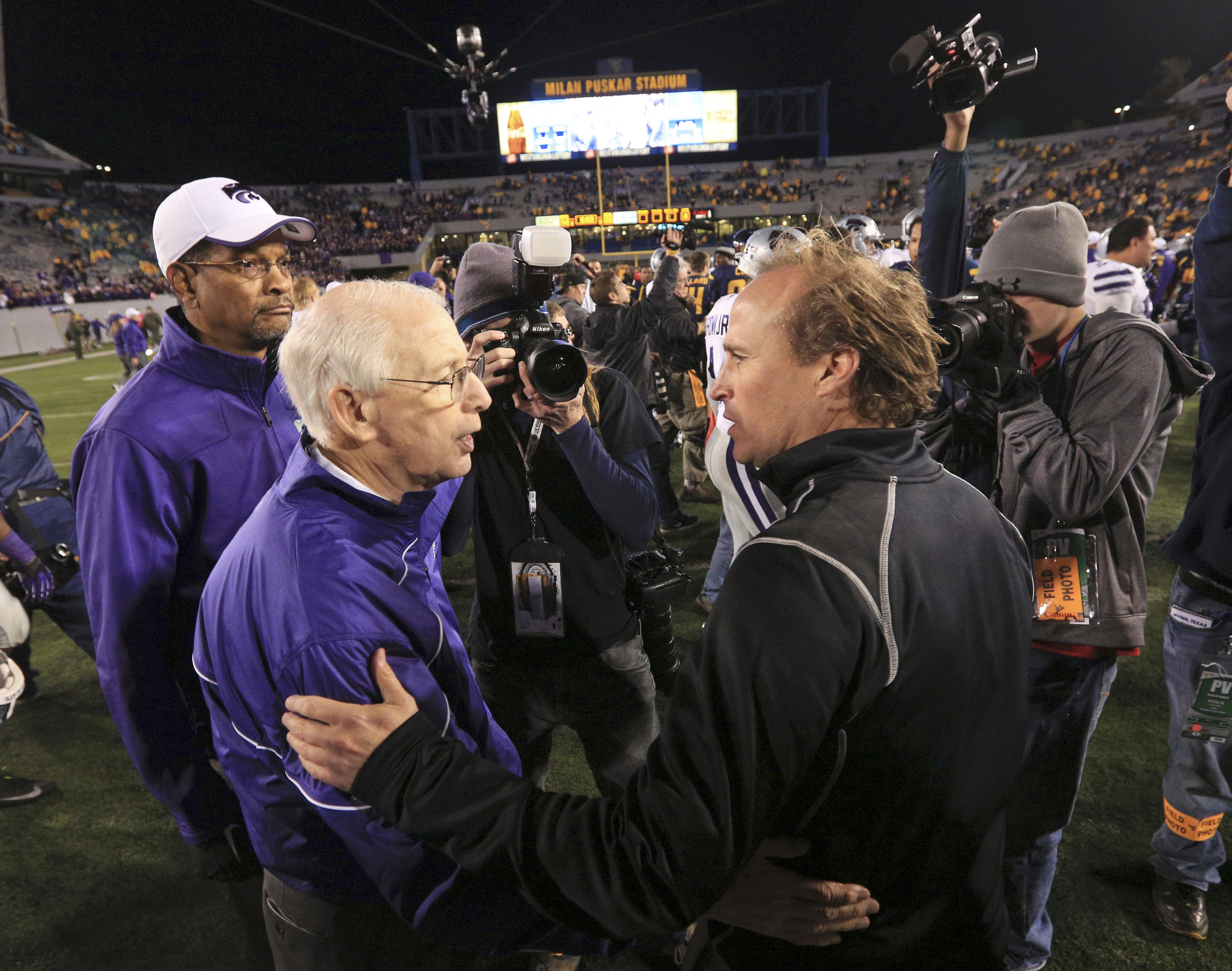 FILE - In this Oct. 20, 2012, file photo, Kansas State coach Bill Snyder, front left, greets West Virginia coach Dana Holgorsen meet following an NCAA college football game in Morgantown, W.Va. The two teams meet on Saturday in Morgantown (AP Photo/Christ