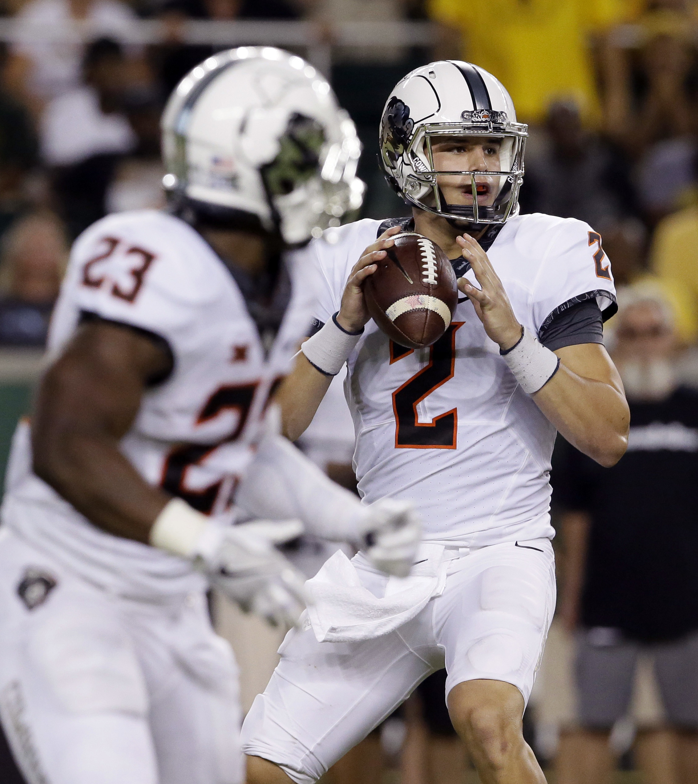 FILE - I this Sept. 24, 2016, file photo, Oklahoma State quarterback Mason Rudolph (2) looks to pass as running back Rennie Childs (23) looks back during an NCAA college football game against Baylor in Waco, Texas. Oklahoma State takes on Texas on Saturda