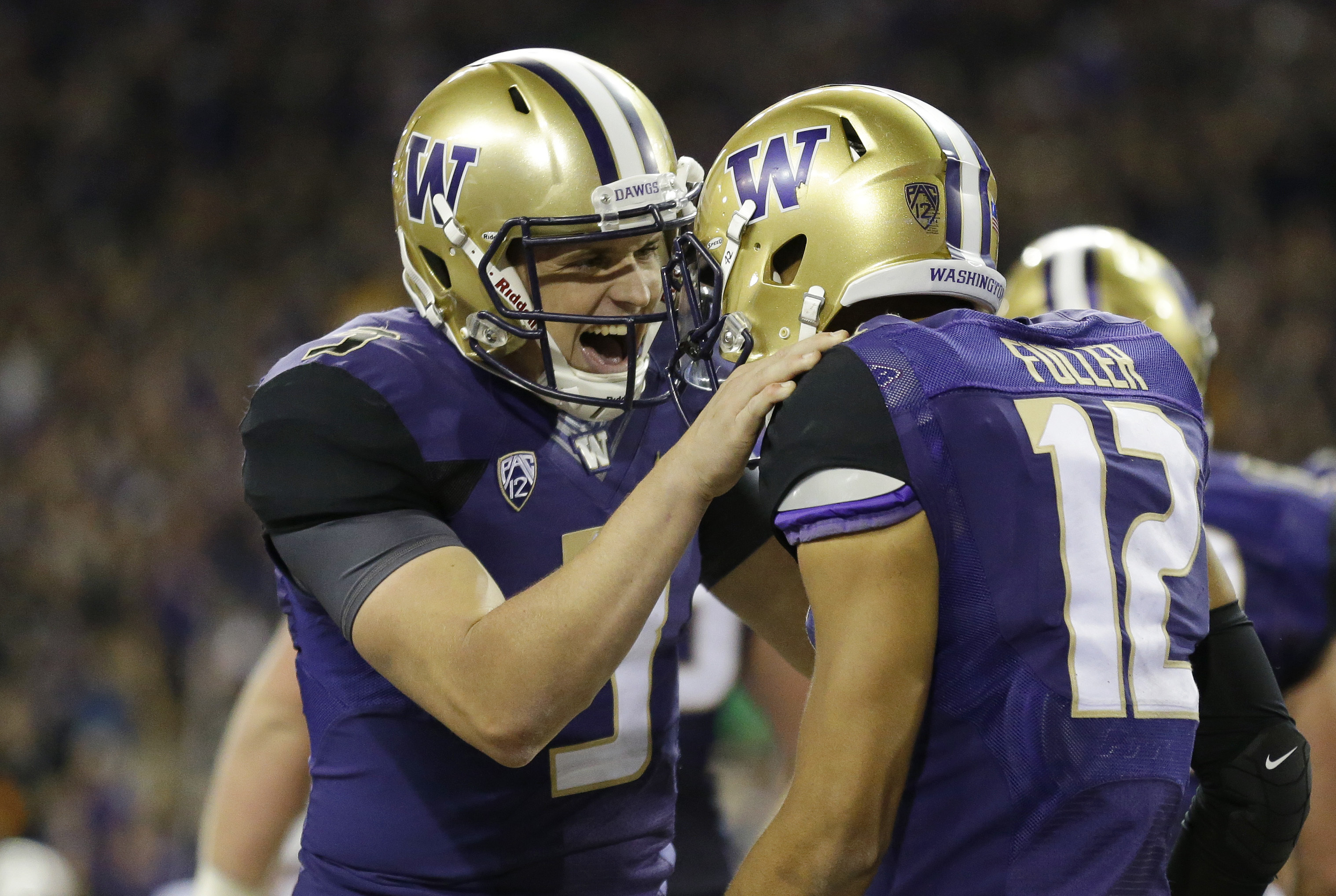 Washington quarterback Jake Browning, left, celebrates with wide receiver Aaron Fuller (12) after Fuller caught a pass from Browning for a touchdown during the second half of an NCAA college football game against Stanford on Friday, Sept. 30, 2016, in Sea