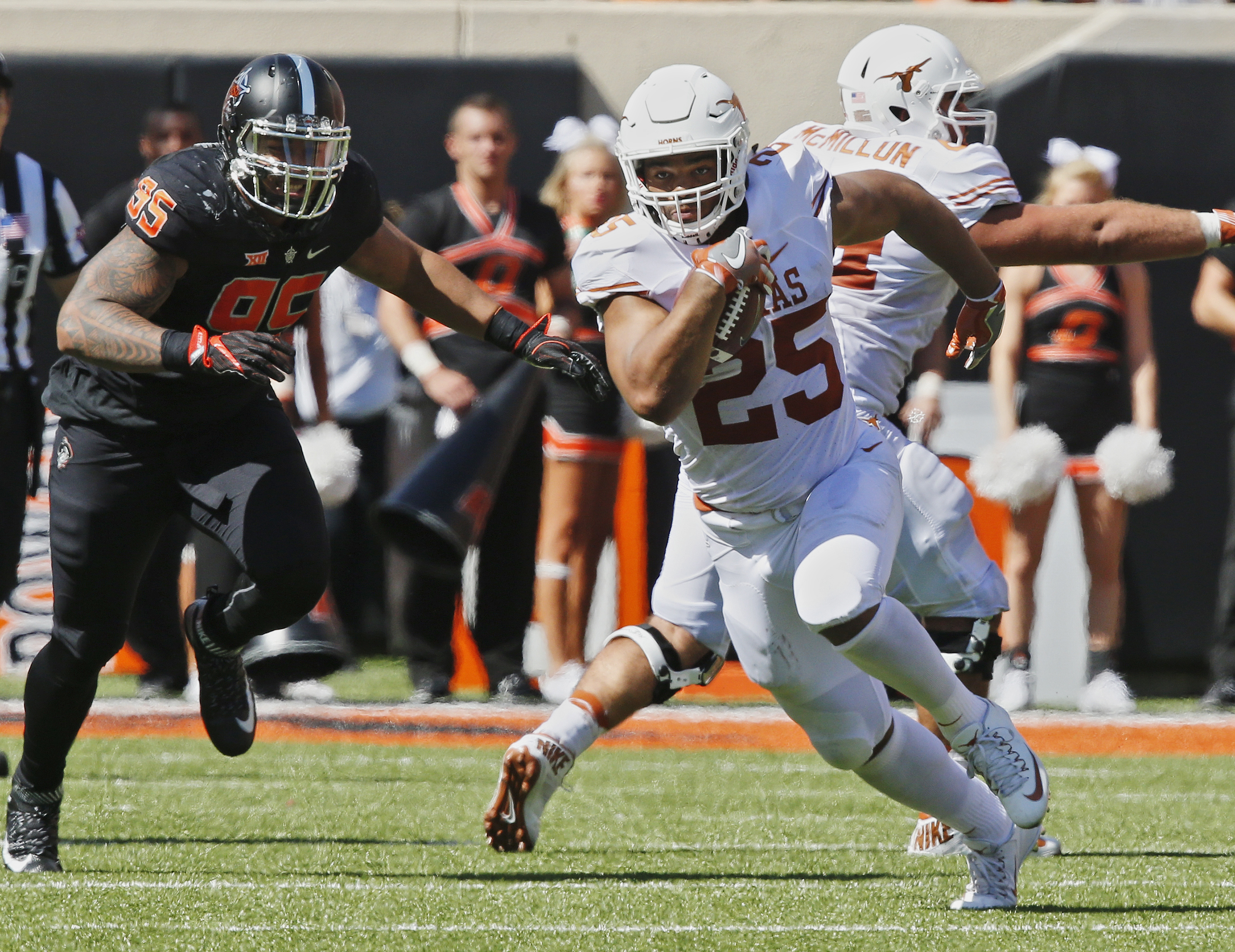 Texas running back Chris Warren III (25) carries past Oklahoma State defensive tackle Vili Leveni (95) in the first half of an NCAA college football game in Stillwater, Okla., Saturday, Oct. 1, 2016.  Oklahoma State won 49-31. (AP Photo/Sue Ogrocki)