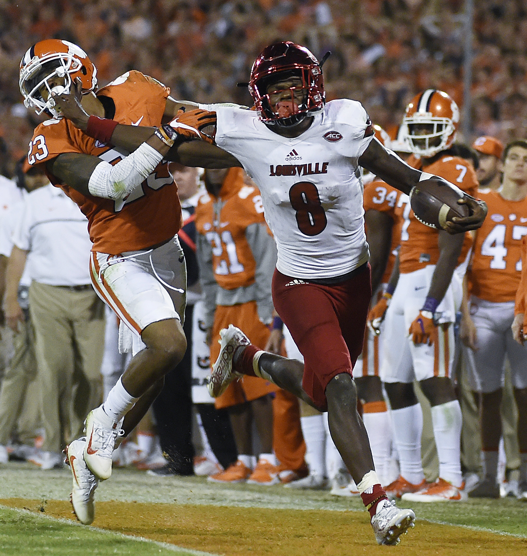 FILE - In this Oct. 1, 2016, file photo, Louisville quarterback Lamar Jackson (8) stiff-arms Clemson safety Van Smith (23) as he goes out of bounds during the second half of an NCAA college football game in Clemson, S.C.  With enough games played to have