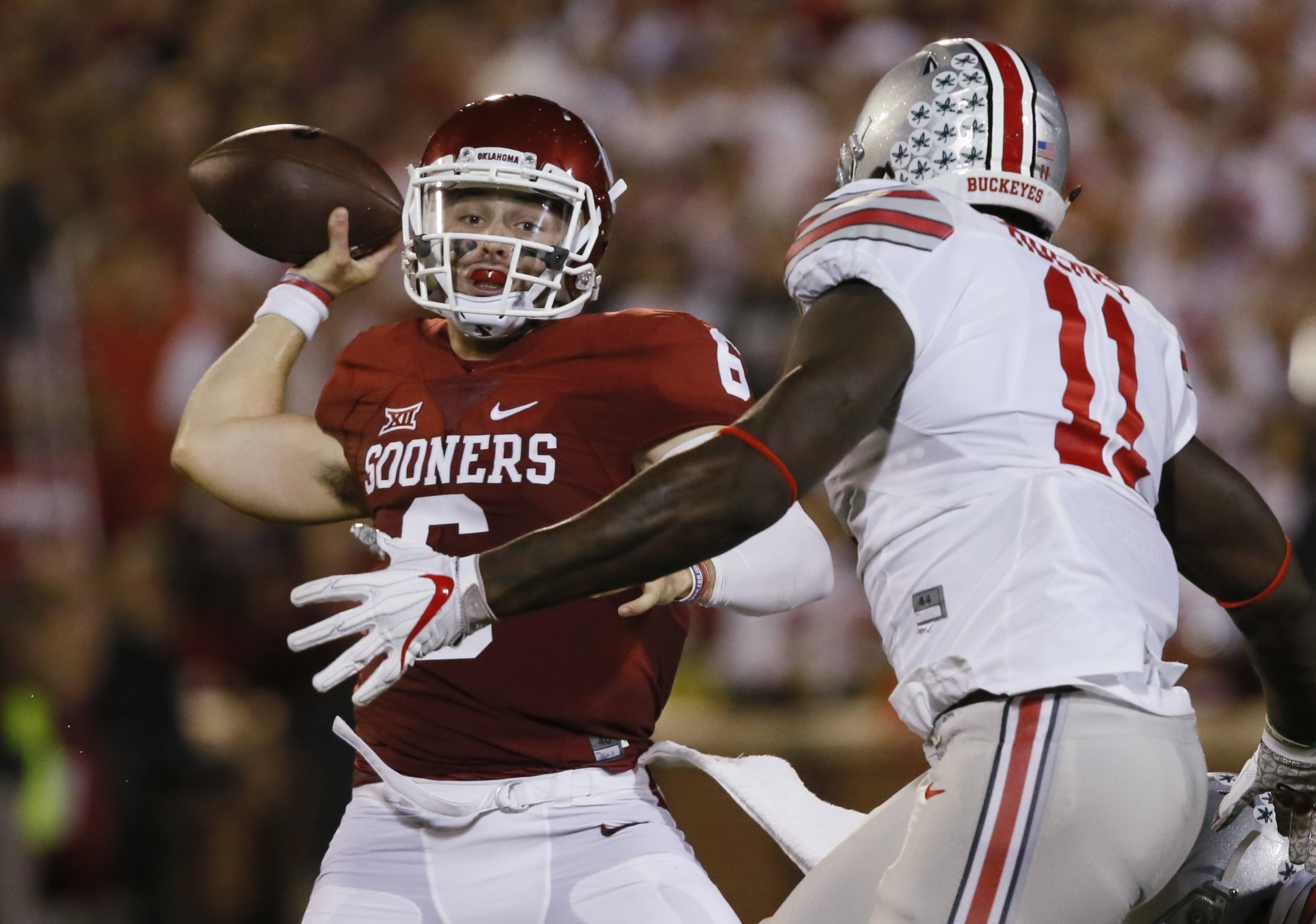In this Saturday, Sept. 17, 2016, photo, Oklahoma quarterback Baker Mayfield, left, throws under pressure from Ohio State defensive end Jalyn Holmes (11) in the first quarter of an NCAA college football game in Norman, Okla. Mayfield has accomplished a gr