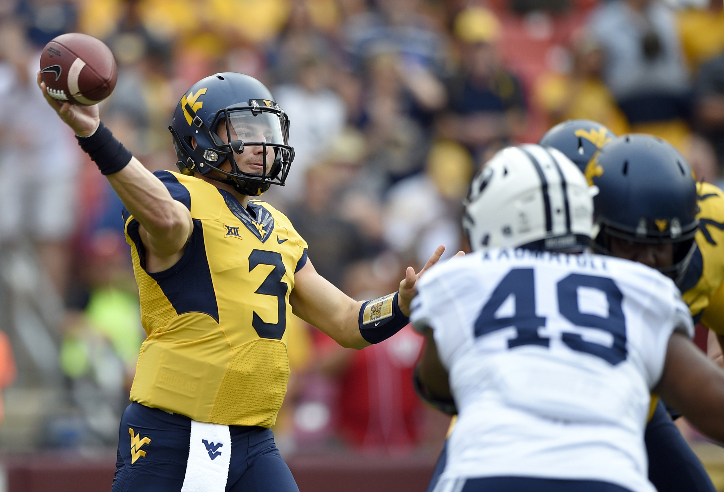 FILE - In this Sept. 24, 2016, file photo, West Virginia quarterback Skyler Howard (3) passes while pressured by BYU defensive lineman Moses Kaumatule (49) during the first half of an NCAA college football game Landover, Md. West Virginia has this week of