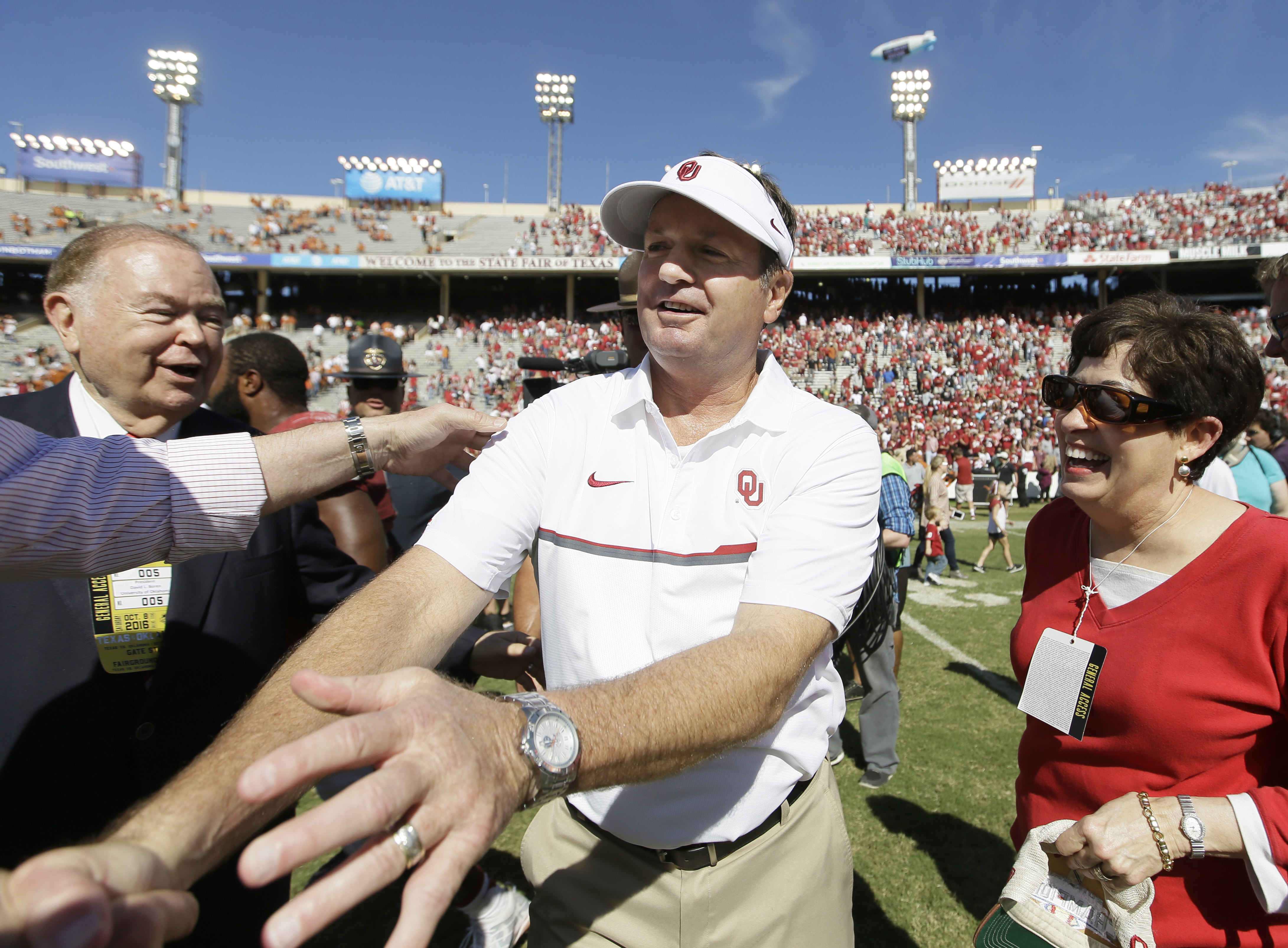 Oklahoma head coach Bob Stoops, center, is congratulated after their 45-40 win over Texas in an NCAA college football game in Dallas Saturday, Oct. 8, 2016. (AP Photo/LM Otero)