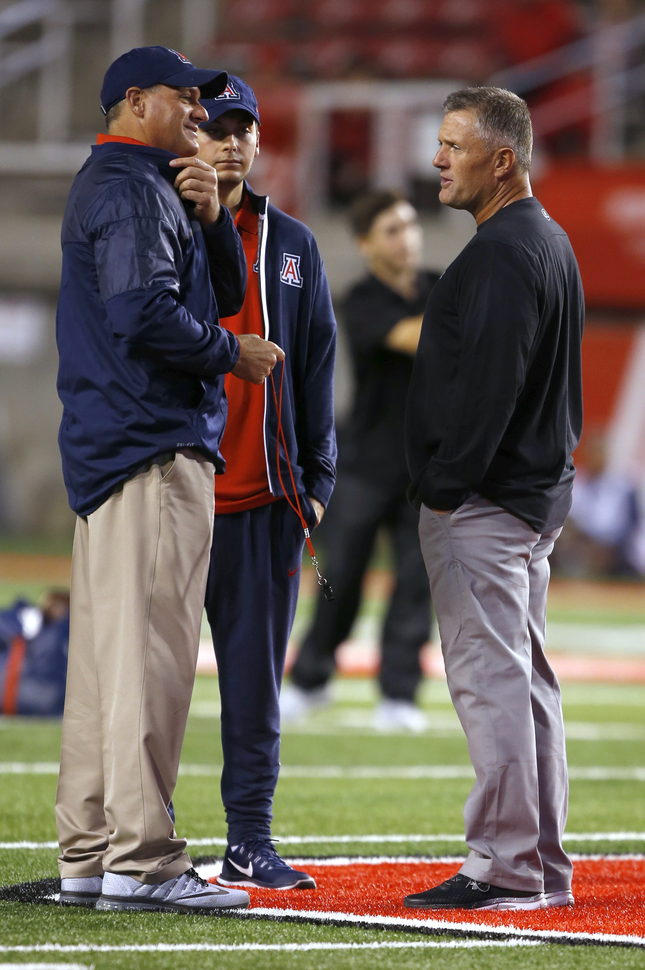 Arizona coach Rich Rodriguez, left, talks with Utah coach Kyle Whittingham, right, before an NCAA college football game, Saturday, Oct. 8, 2016, in Salt Lake City. (AP Photo/George Frey)