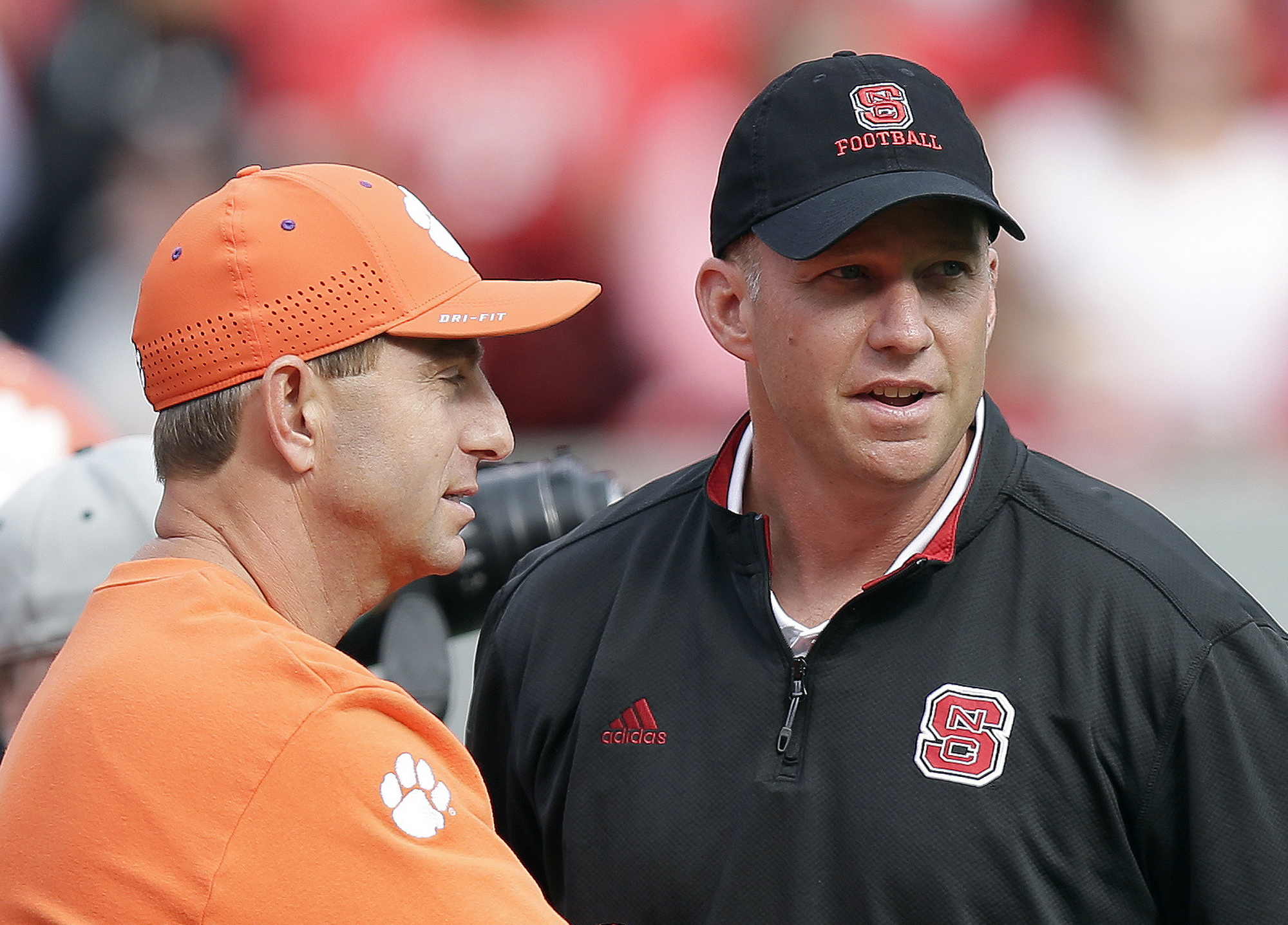 FILE - In this Oct. 31, 2015, file photo, Clemson coach Dabo Swinney, left, and North Carolina State coach Dave Doeren chat before an NCAA college football game in Raleigh, N.C. NC State is looking to turn the Atlantic Coast Conference from a runaway into