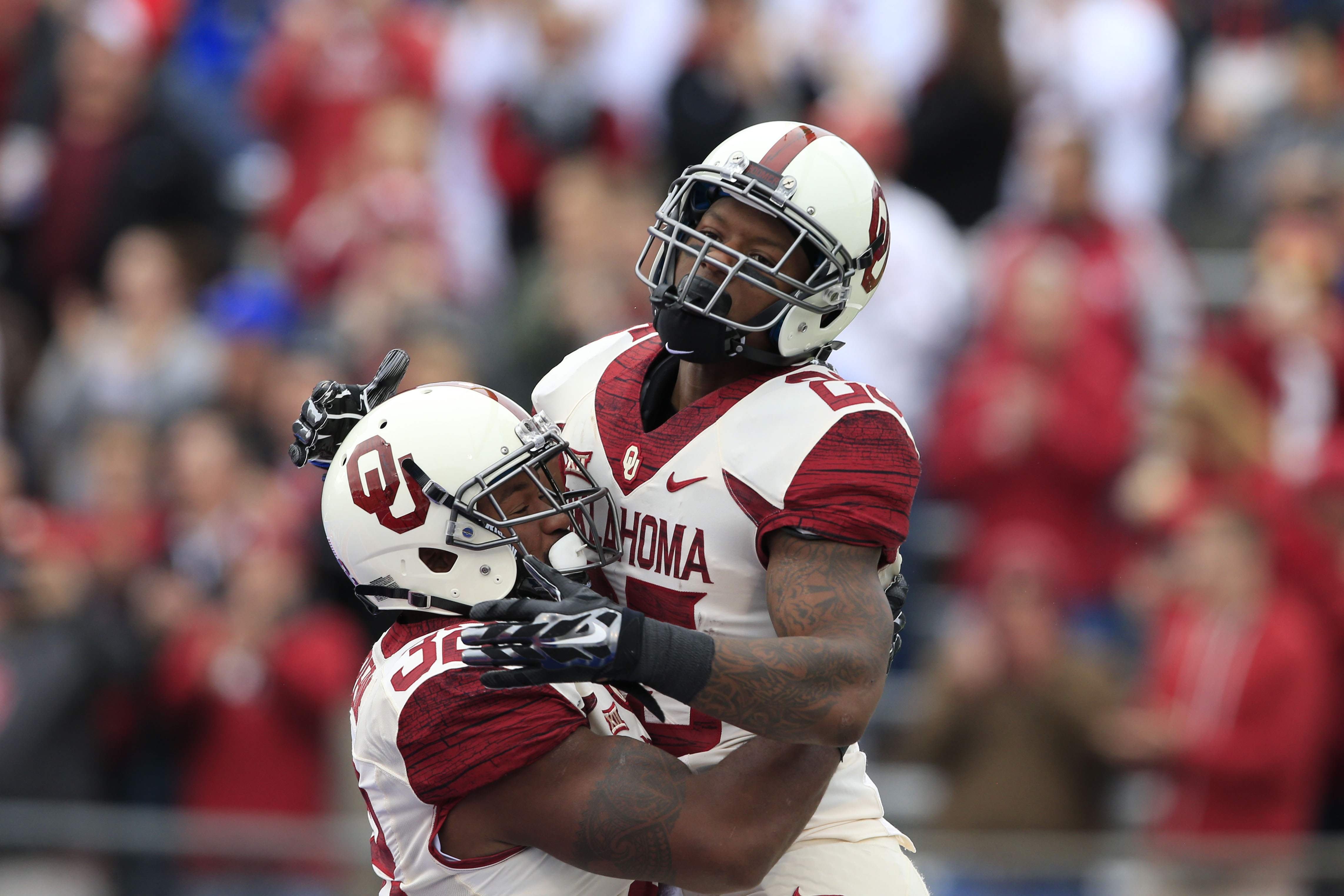 FILE- In this Oct. 31, 2015, file photo, Oklahoma running backs Joe Mixon, right, and Samaje Perine (32) celebrate during the first half of an NCAA college football game against Kansas in Lawrence, Kan. There are several different running combos in the Bi
