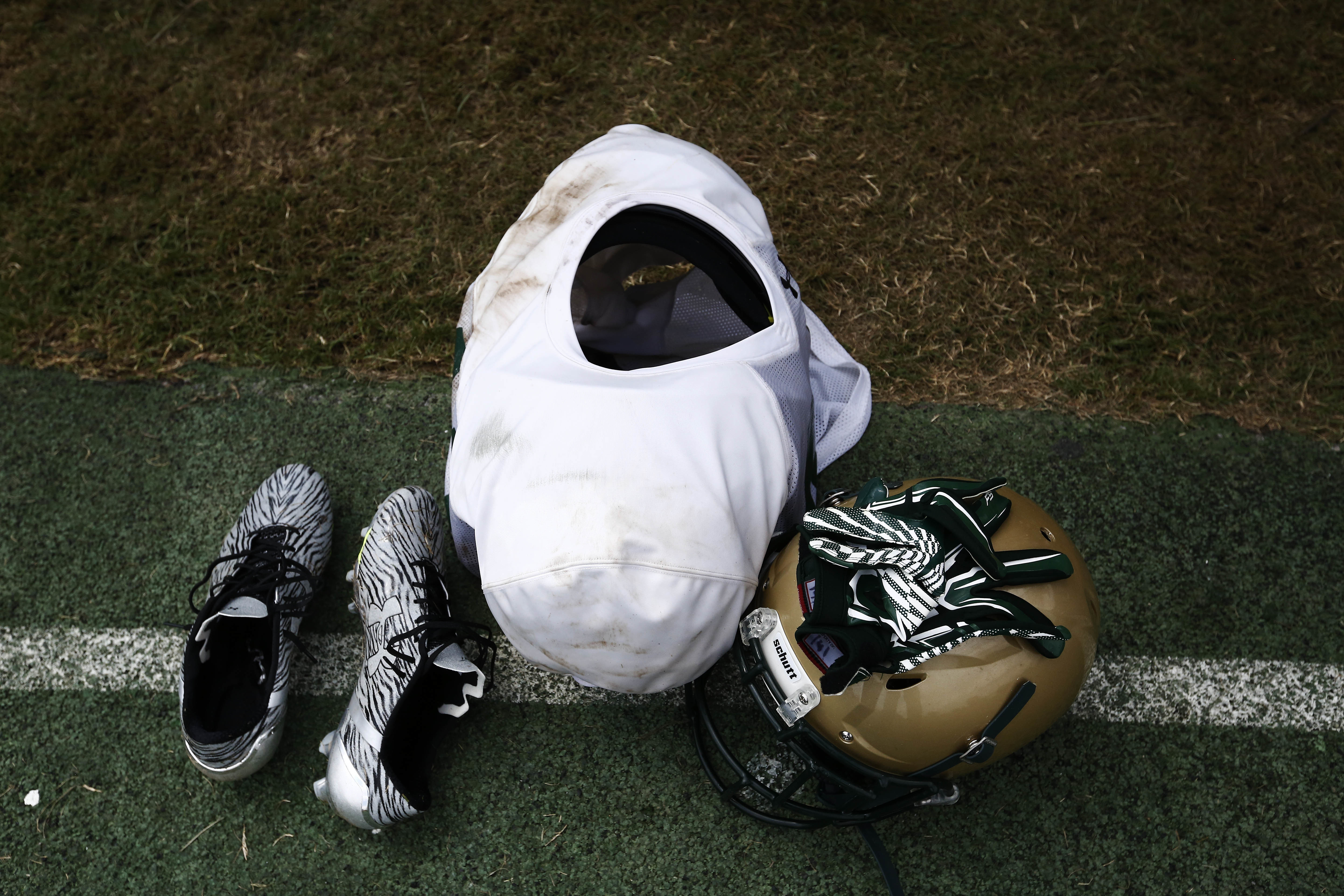 A UAB football player's gear sits on the practice field, Thursday, Aug. 25, 2016, in Birmingham, Ala. A program shut down for lack of financial support in December 2014 is coming back bigger and better, only the wins are coming on the balance sheet instea