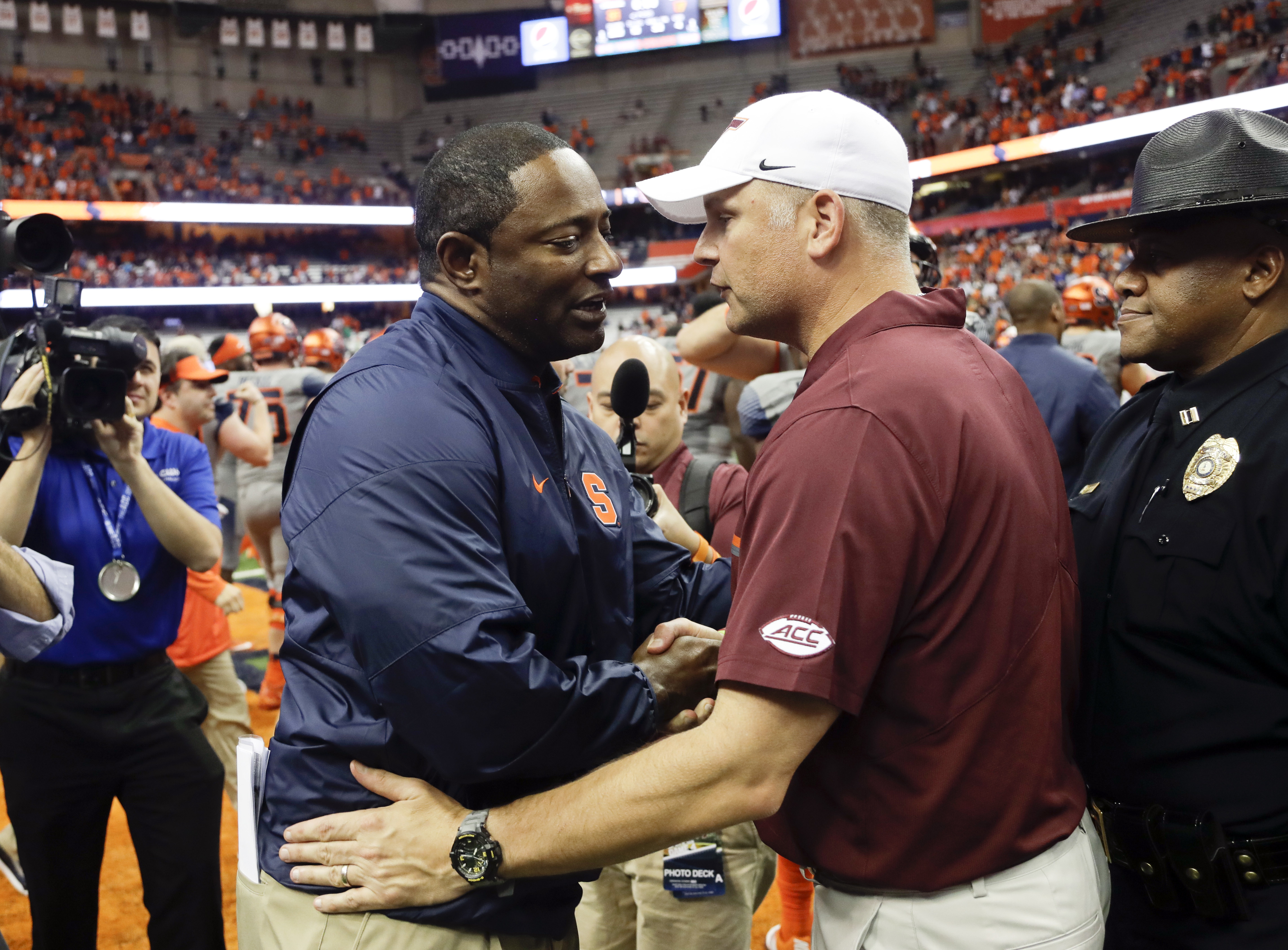 Syracuse head coach Dino Babers, left, and Virginia Tech head coach Justin Fuente talk after an NCAA college football game on Saturday, Oct. 15, 2016, in Syracuse, N.Y. Syracuse won 31-17. (AP Photo/Mike Groll)
