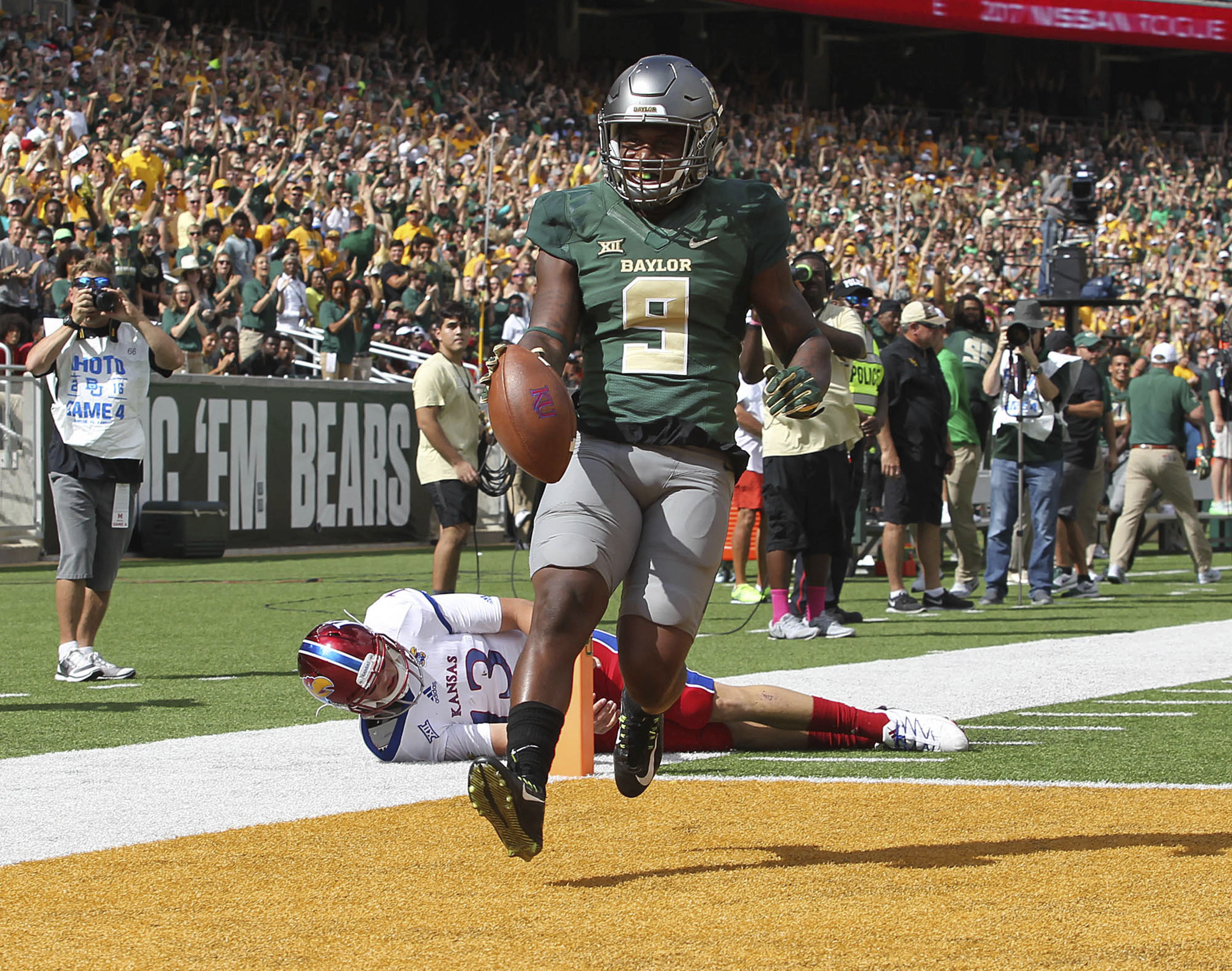 Baylor cornerback Ryan Reid scores on an interception over Kansas quarterback Ryan Willis (13) in the first half of an NCAA college football game, Saturday, Oct. 15, 2016, in Waco, Texas. Baylor won 49-7. (Jerry Larson/Waco Tribune Herald via AP)