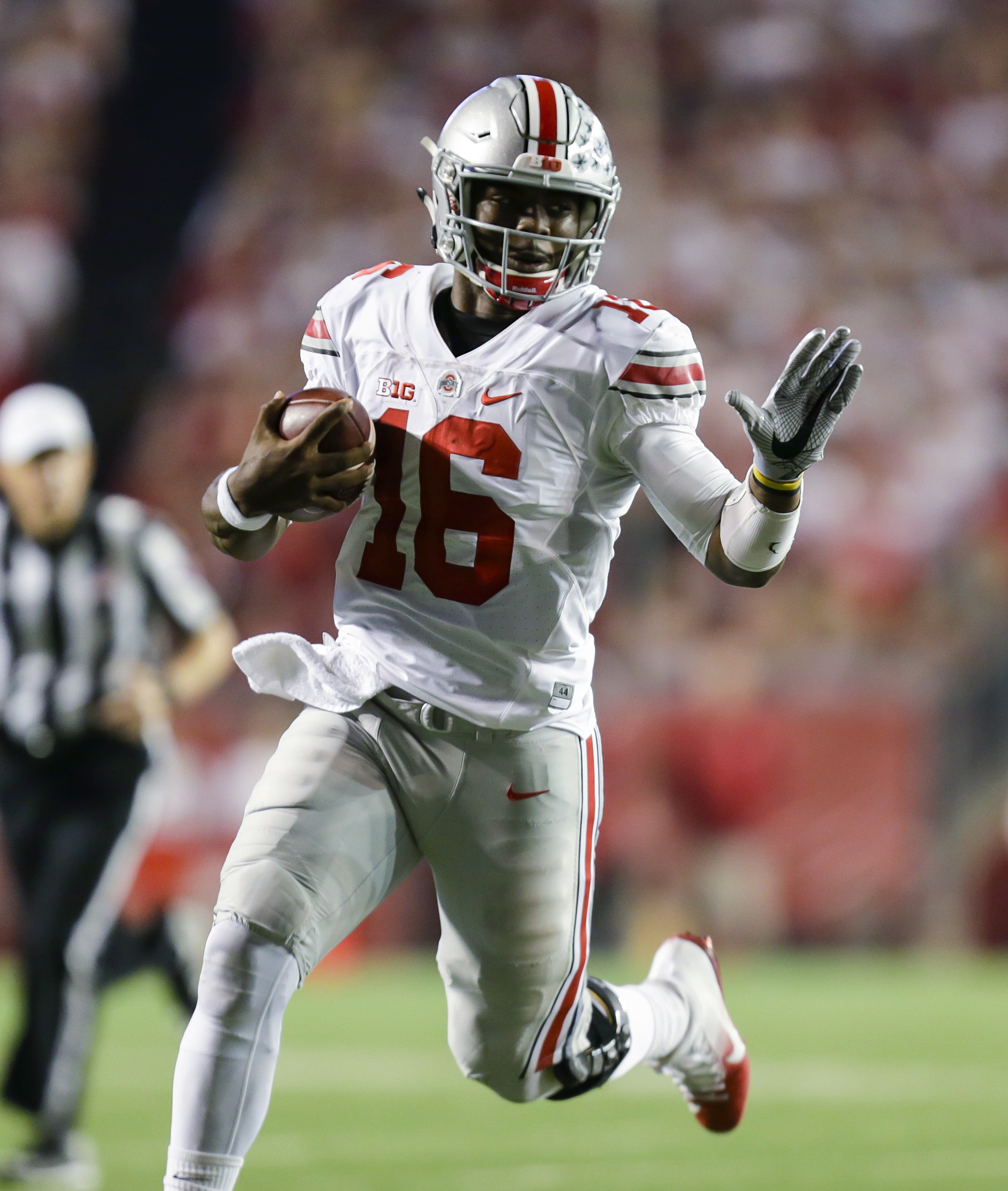 FILE - In this Oct. 15, 2016, file photo, Ohio State quarterback J.T. Barrett (16) scrambles against Wisconsin during the first half of an NCAA college football game, in Madison, Wis. Barrett was big-time in prime time last week and now he has two more sh