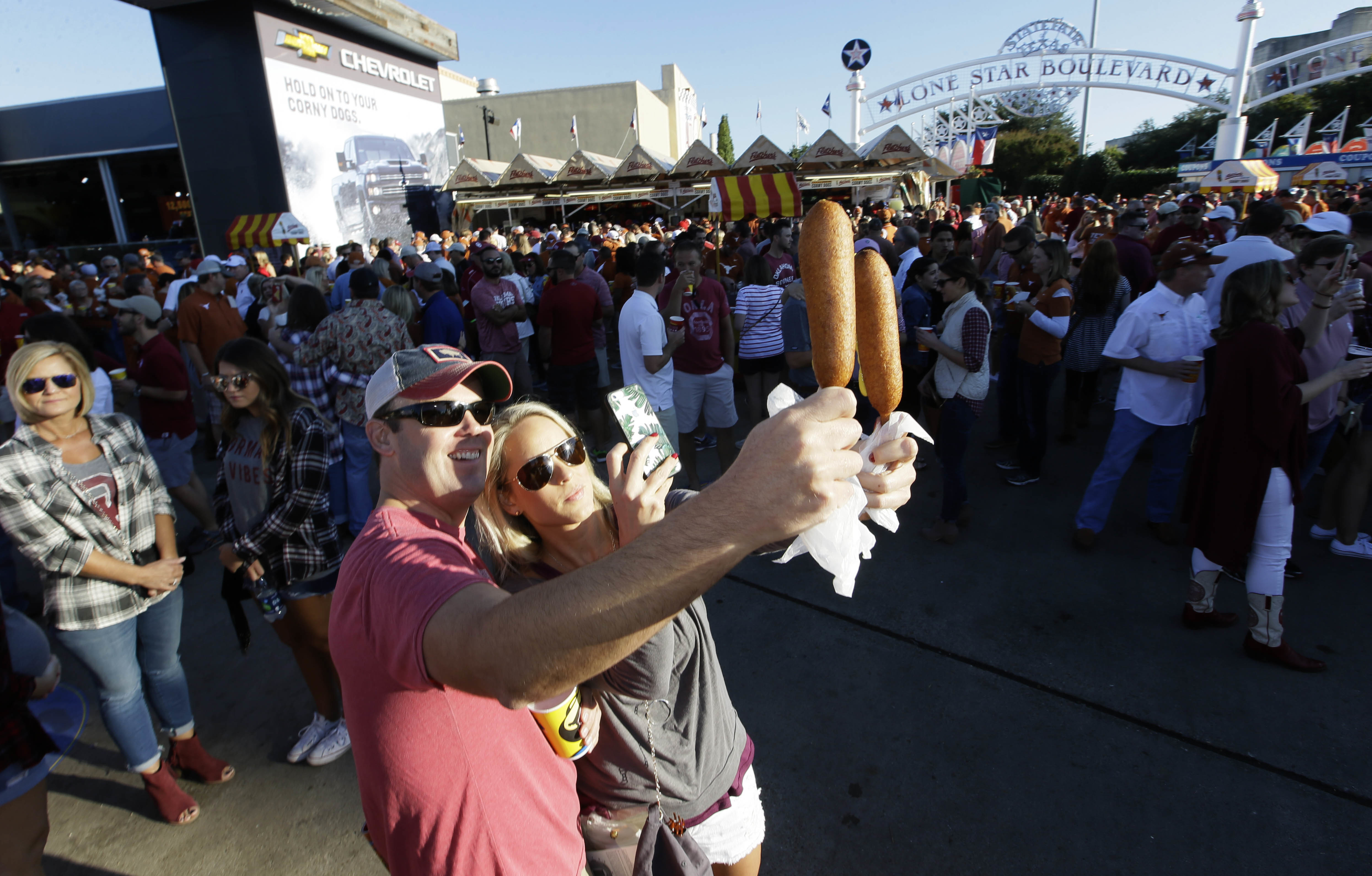 FILE - In this Oct. 8, 2016, file photo, Gwin Huey, right, and her husband, Ryan Huey, make a photo of their corn dogs at the state fair before an NCAA college football game between Texas and Oklahoma in Dallas.Now that the Big 12 has decided to stay at 1
