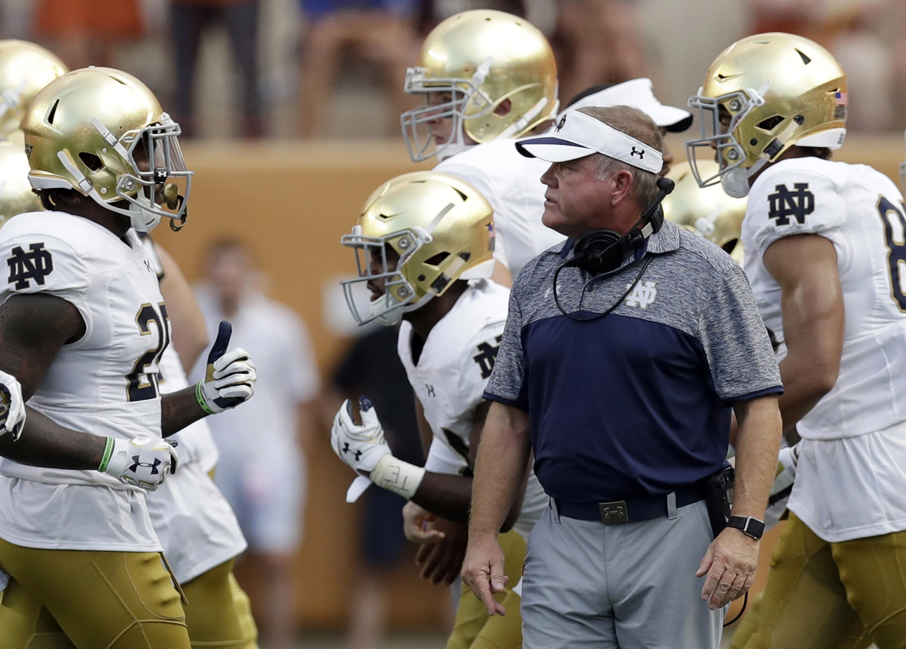 FILE - In this Sunday, Sept. 4, 2016, file photo, Notre Dame head coach Brian Kelly, center, watches as his players run off the field during the first half of an NCAA college football game against Texas in Austin, Texas. Simpler and louder have meant bett