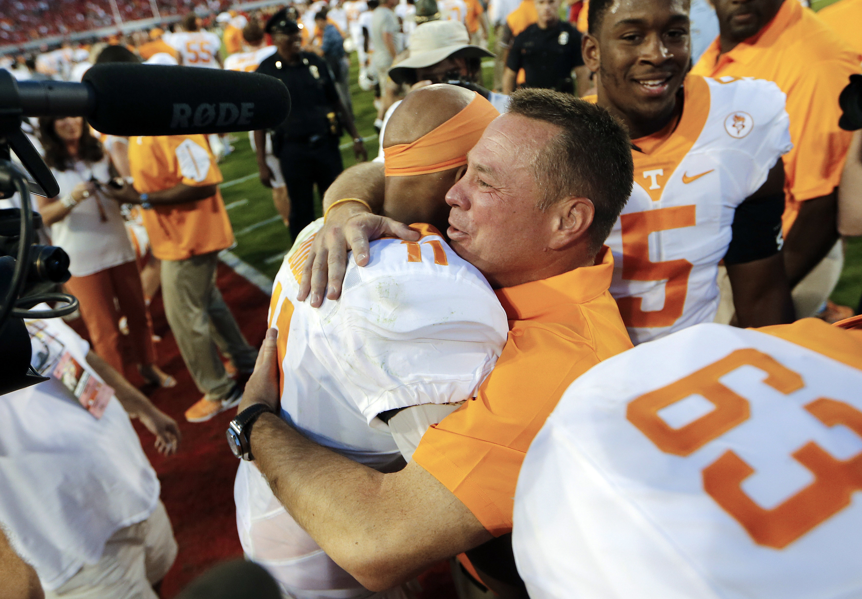 FILE- Int his Oct. 1, 2016, file photo, Tennessee head coach Butch Jones hugs quarterback Joshua Dobbs (11) after defeating Georgia 34-31 in an NCAA college football game in Athens, Ga. Tennessee's bye week came at an ideal spot for the 18th-ranked Volunt