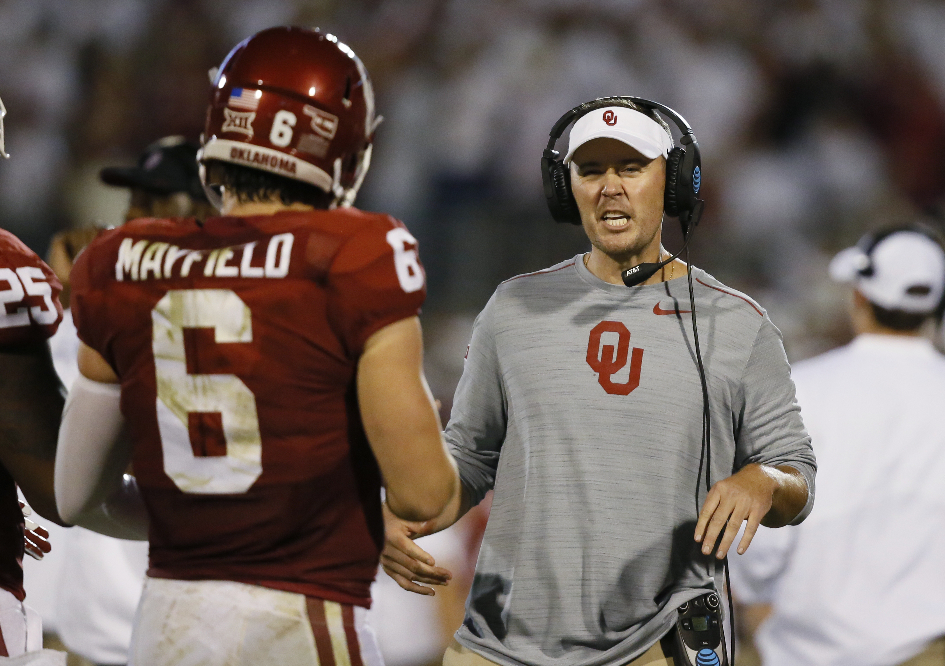 FILE - In this Sept. 17, 2016, file photo, Oklahoma offensive coordinator Lincoln Riley, right, talks to quarterback Baker Mayfield (6) during an NCAA college football game against Ohio State in Norman, Okla. Riley has taken some of the air out of the Air