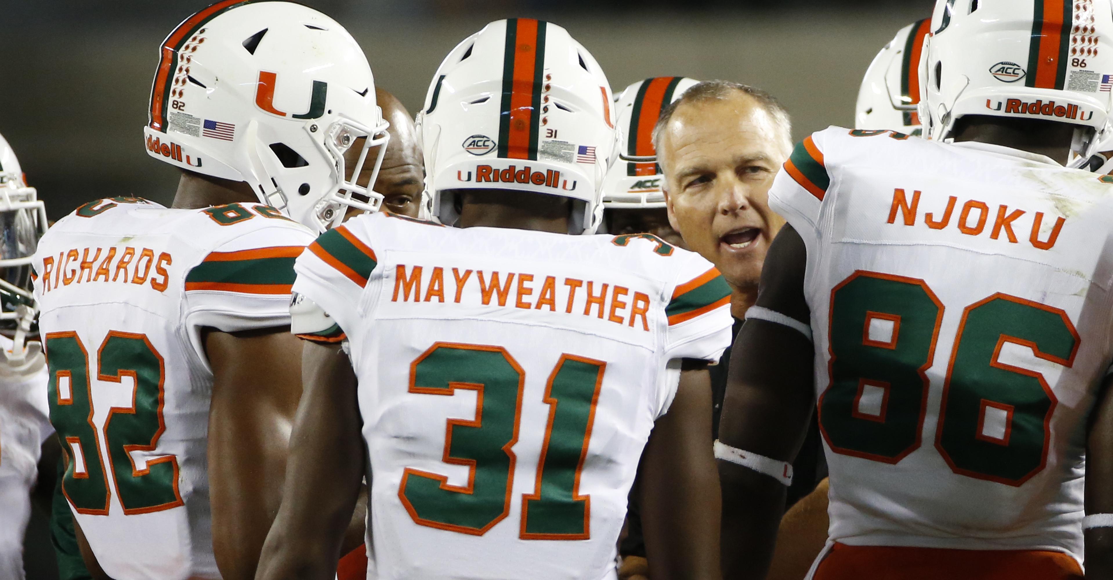 Miami head coach Mark Richt talks to his team during the second half of an NCAA college football game against Virginia Tech at Lane stadium in Blacksburg, Va., Thursday, Oct. 20, 2016. Virginia Tech defeated Miami 37-16. (AP Photo/Steve Helber)