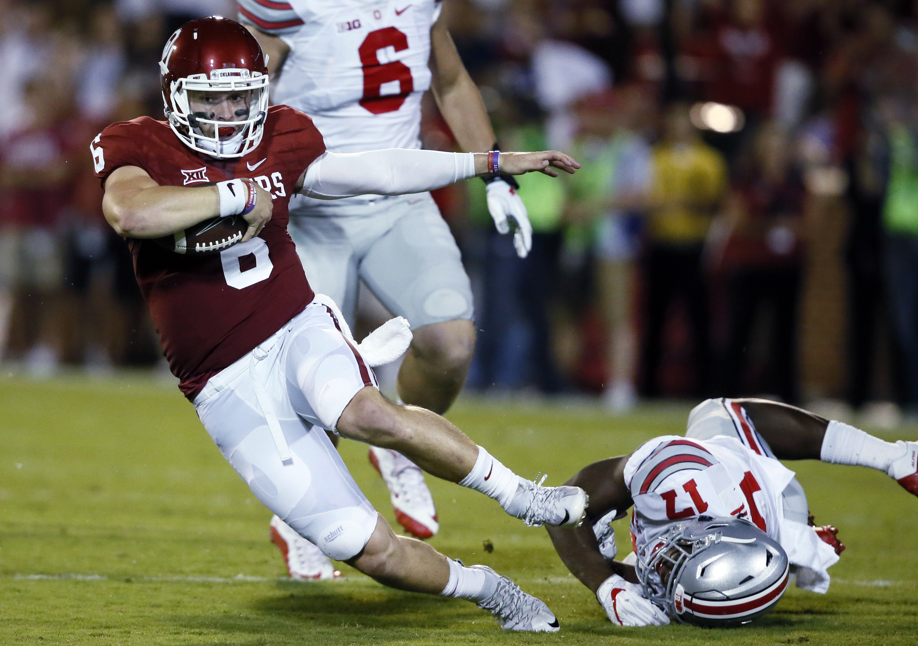 FILE - In this Sept. 17, 2016, file photo, Oklahoma quarterback Baker Mayfield (6) fights off a tackle by Ohio State linebacker Jerome Baker, right, during an NCAA college football game in Norman, Okla. Mayfield came into the season as one of the big-name