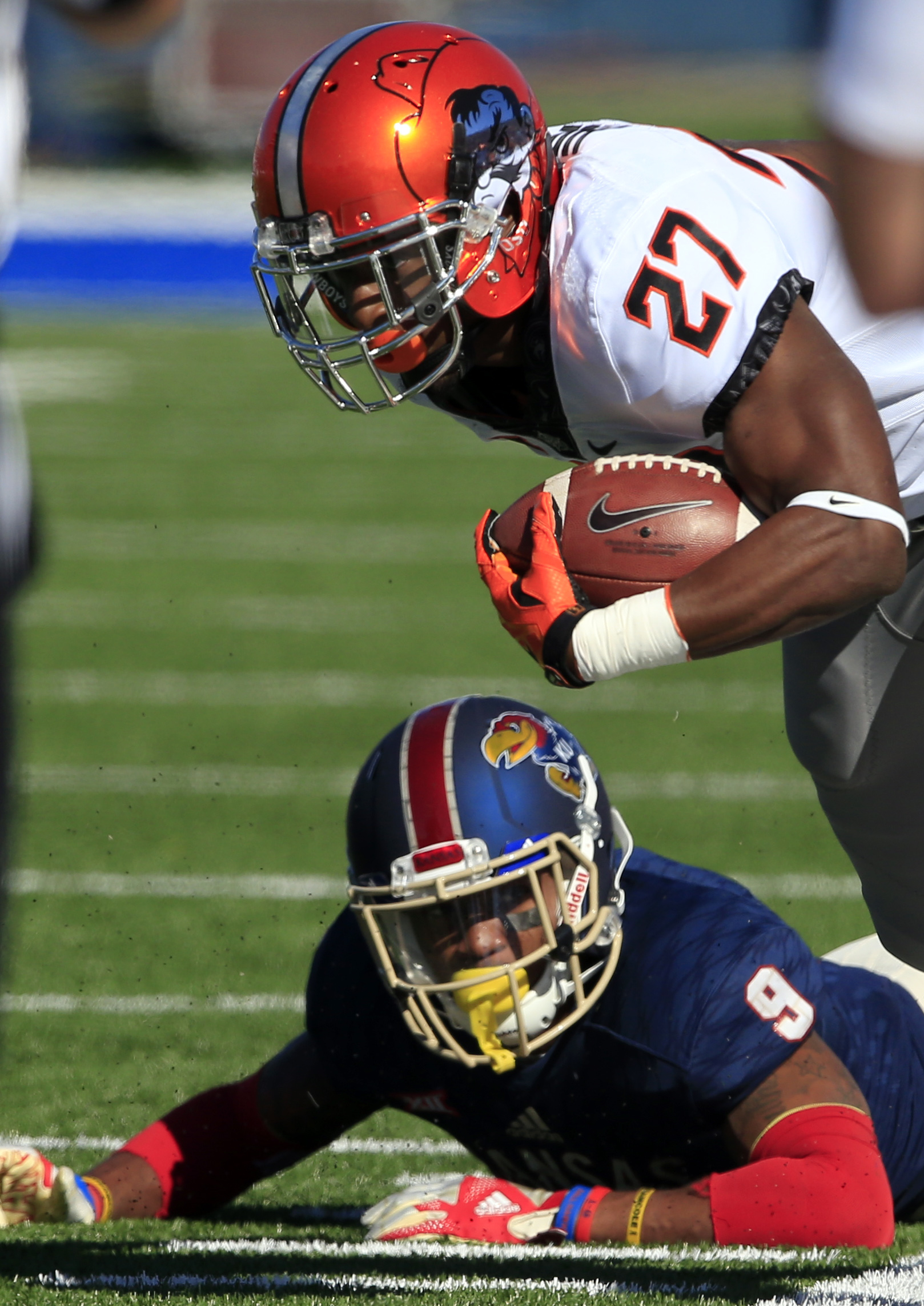 Oklahoma State running back Justice Hill (27) is forced out of bounds by Kansas safety Fish Smithson (9) during the first half of an NCAA college football game in Lawrence, Kan., Saturday, Oct. 22, 2016. (AP Photo/Orlin Wagner)