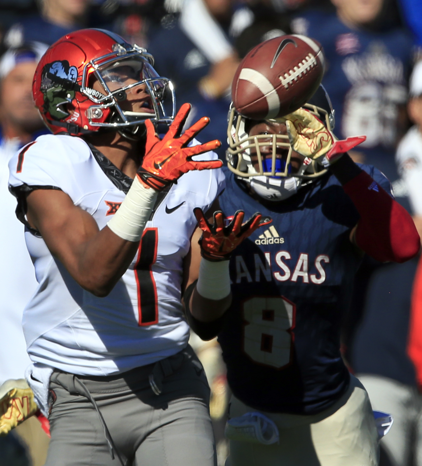 Oklahoma State wide receiver Jalen McCleskey (1) catches a pass while covered by Kansas cornerback Brandon Stewart (8) during the first half of an NCAA college football game in Lawrence, Kan., Saturday, Oct. 22, 2016. (AP Photo/Orlin Wagner)
