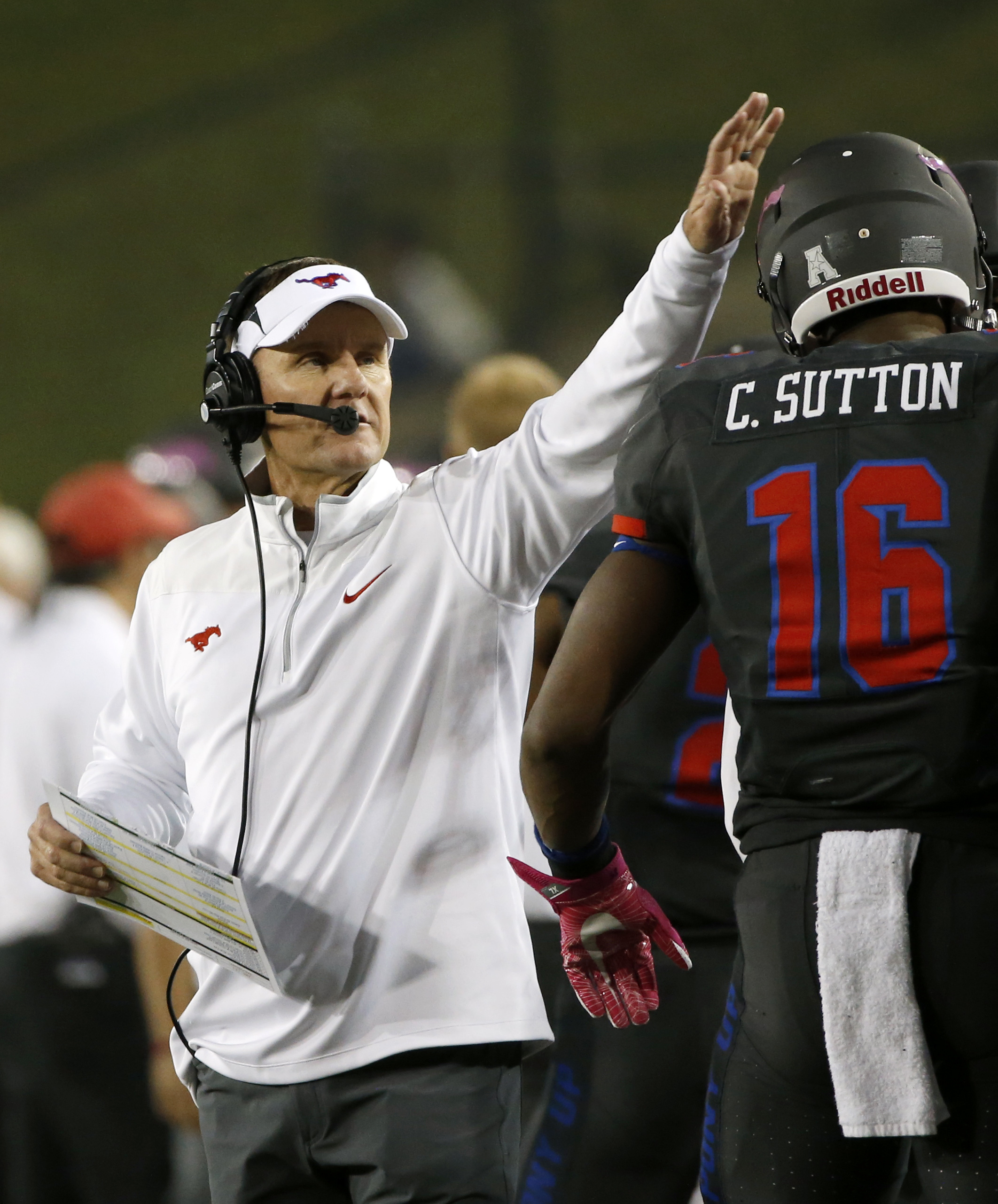 SMU coach Chad Morris welcomes wide receiver Courtland Sutton (16) back to the sideline after Sutton caught a touchdown pass against Houston during the first half of an NCAA college football game, Saturday, Oct. 22, 2016, in Dallas. (AP Photo/Ron Jenkins)