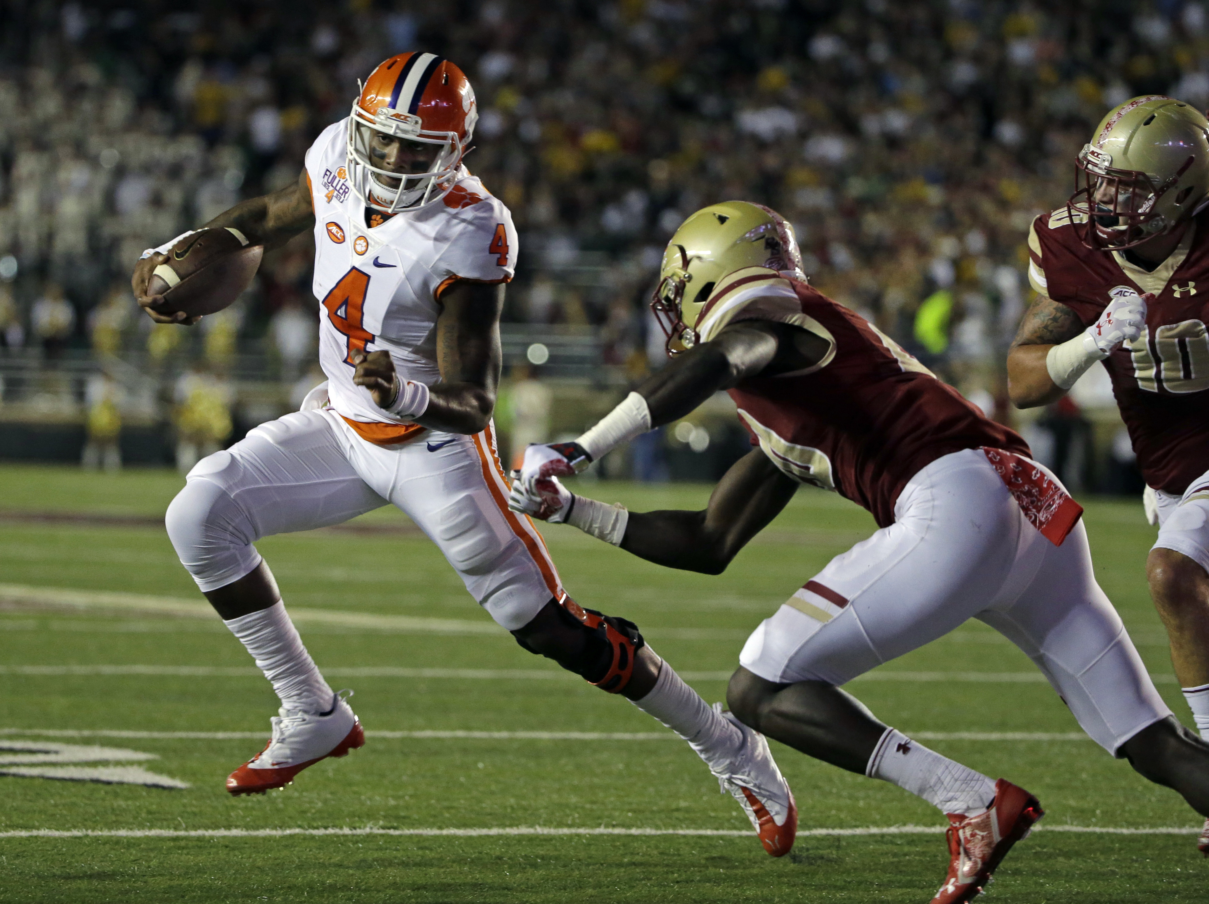 FILE - In this Oct. 7, 2016, file photo, Clemson quarterback Deshaun Watson (4) dashes around Boston College defensive back Isaac Yiadom (20) and linebacker Ty Schwab (10) during the first half of an NCAA college football game, in Boston. Watson is still