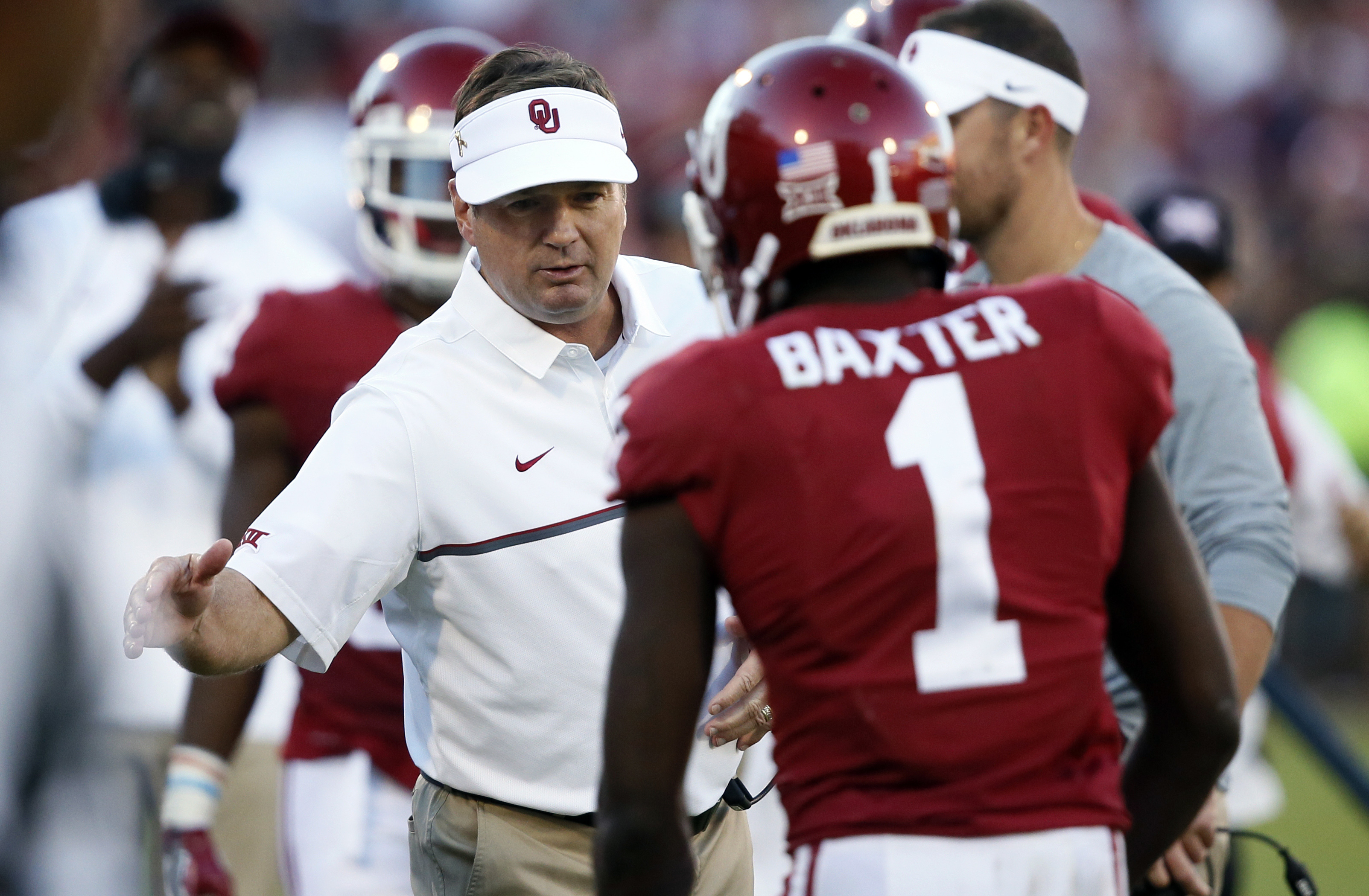 FILE - In this Sept. 1o, 2016, file photo, Oklahoma head coach Bob Stoops, left, greets wide receiver Jarvis Baxter (1) following a touchdown against Louisiana Monroe during an NCAA college football game in Norman, Okla. With Baylor and West Virginia stil