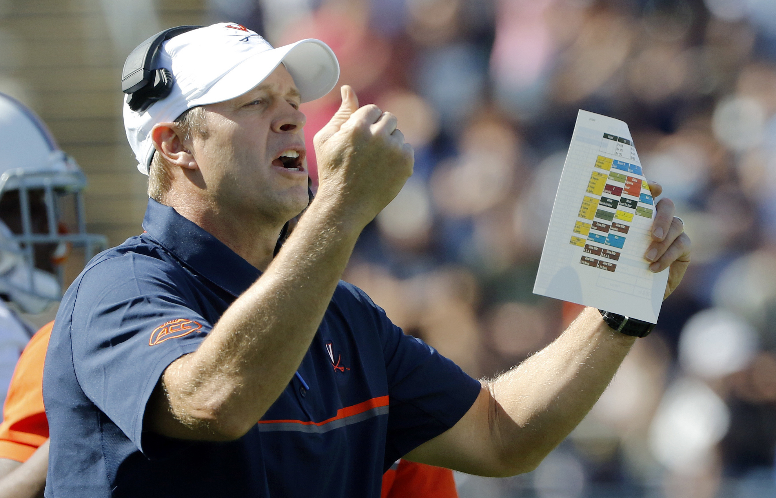 FILE - In this Sept. 17, 2016, file photo, Virginia head coach Bronco Mendenhall instructs from the sideline in the first half of an NCAA college football game against Connecticut in East Hartford, Conn. Louisville and Virginia are heading in opposite dir