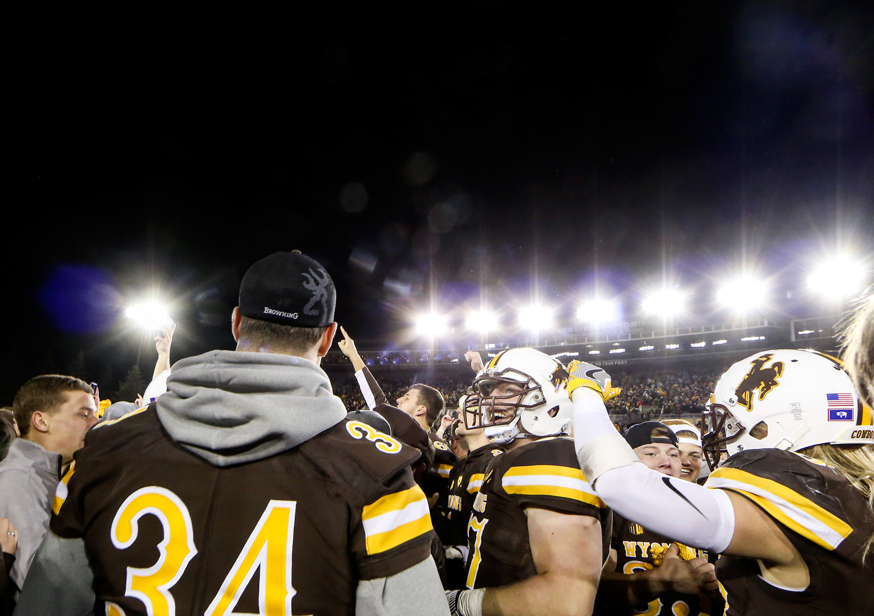Wyoming players and fans celebrate after Wyomilng defeated Boise State 30-28 during an NCAA college football game at War Memorial Stadium in Laramie, Wyo., Saturday Oct. 29, 2016. (AP Photo/Shannon Broderick)