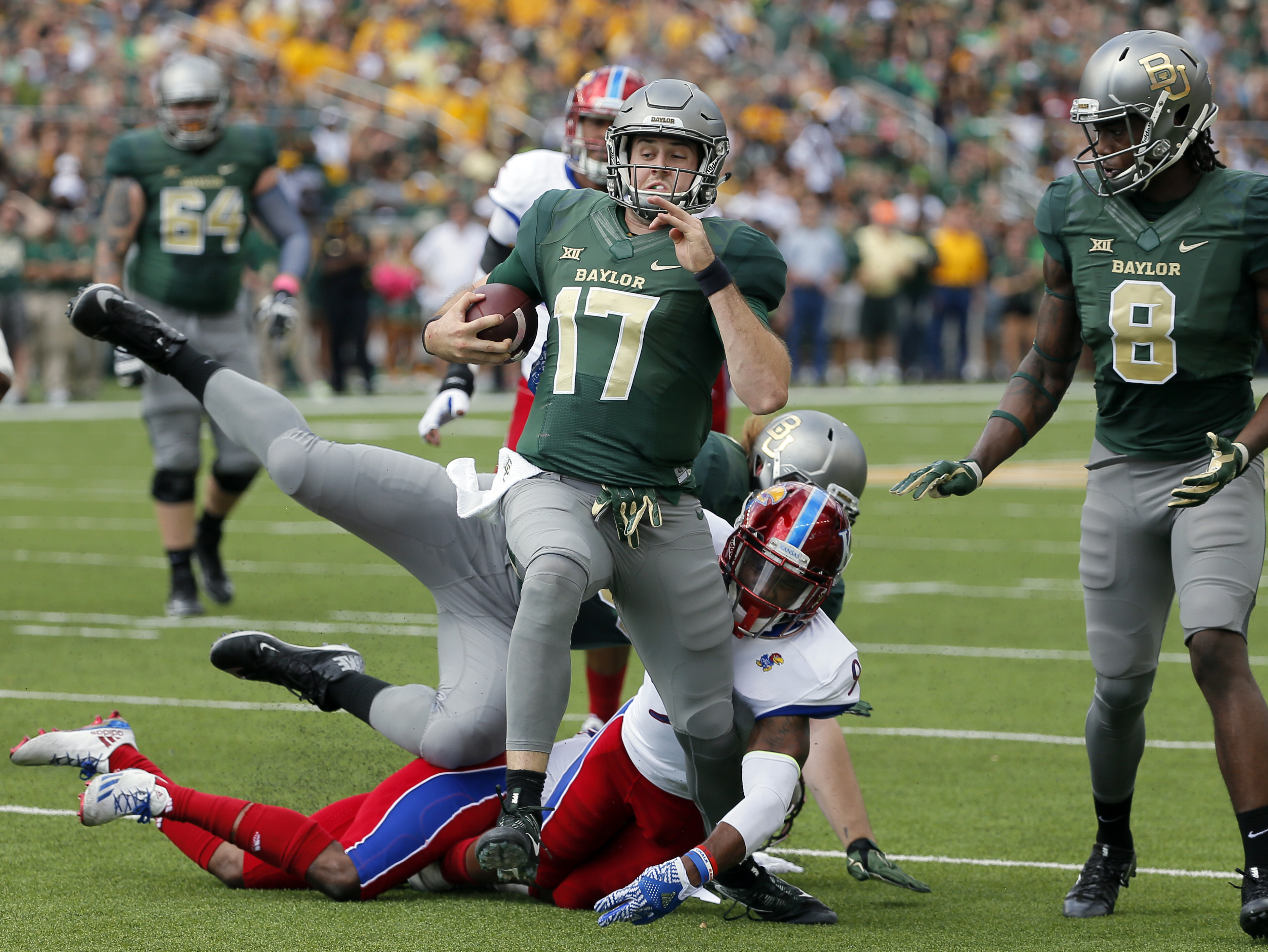 FILE - In this Oct. 15, 2016, file photo, Baylor quarterback Seth Russell (17) escapes a tackle attempt by Kansas safety Fish Smithson (9) as wide receiver Ishmael Zamora (8) watches Russell continue on to the end zone for a touchdown during an NCAA colle