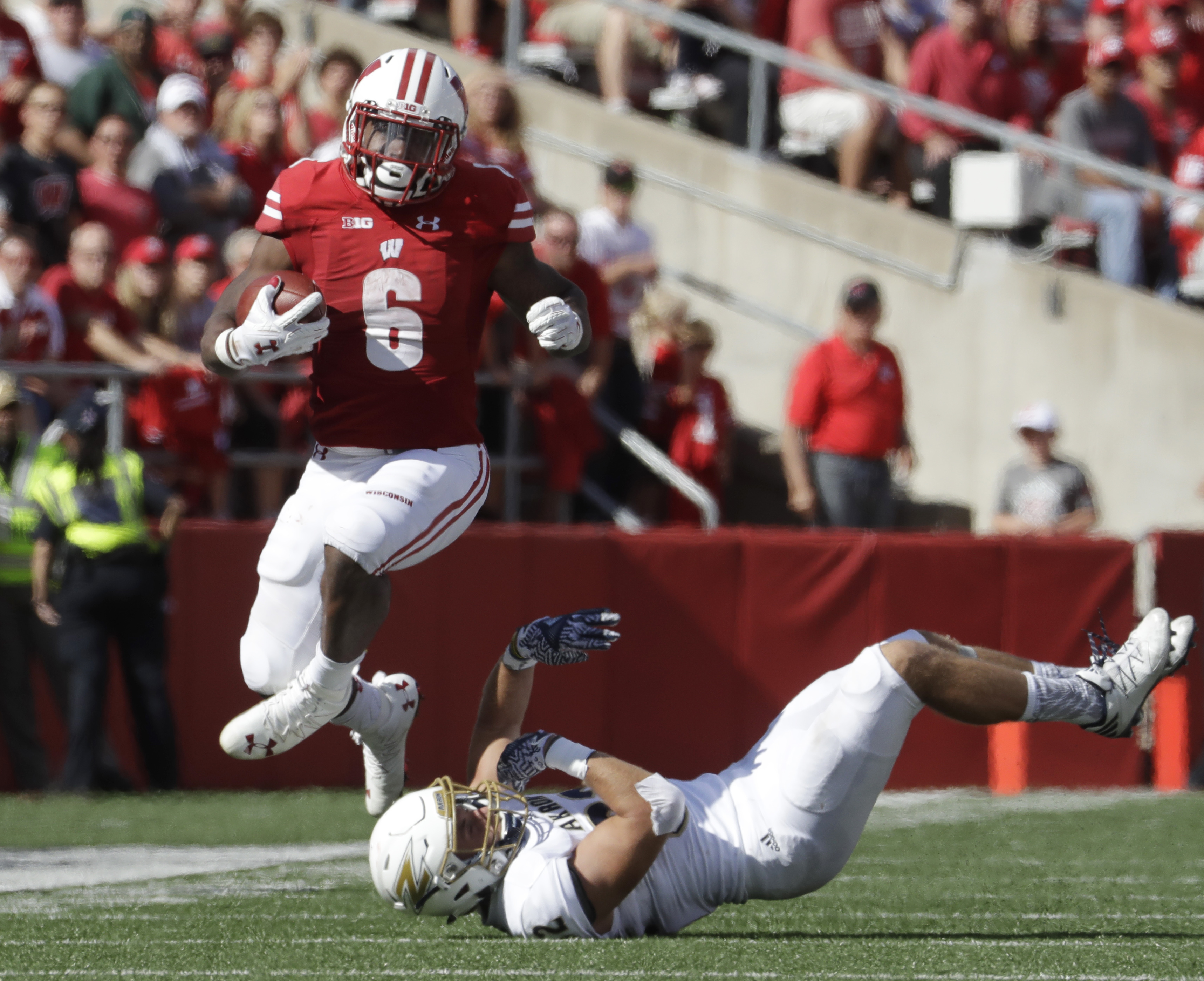 FILE - In this Sept. 10, 2016, file photo, Wisconsin's Corey Clement runs past Akron's Zach Guiser during the first half of an NCAA college football game, in Madison, Wis. The senior came up big in the eighth-ranked Badgers biggest game of the season, but