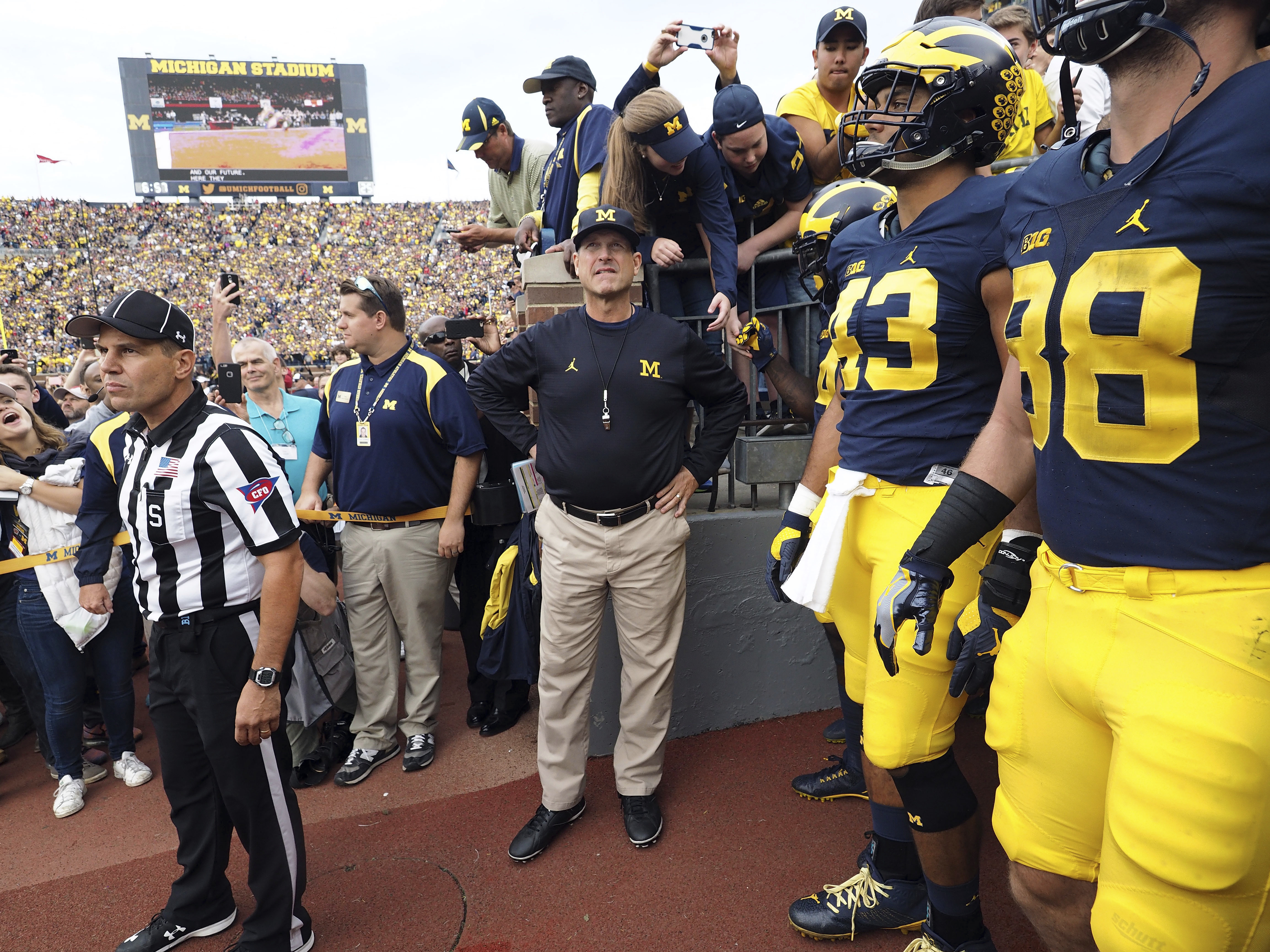FILE - In this Oct. 1, 2016, file photo, Michigan coach Jim Harbaugh, center, waits to take the field with his players before an NCAA college football game against Wisconsin at Michigan Stadium in Ann Arbor, Mich. Michigan faces Maryland on Saturday. (AP