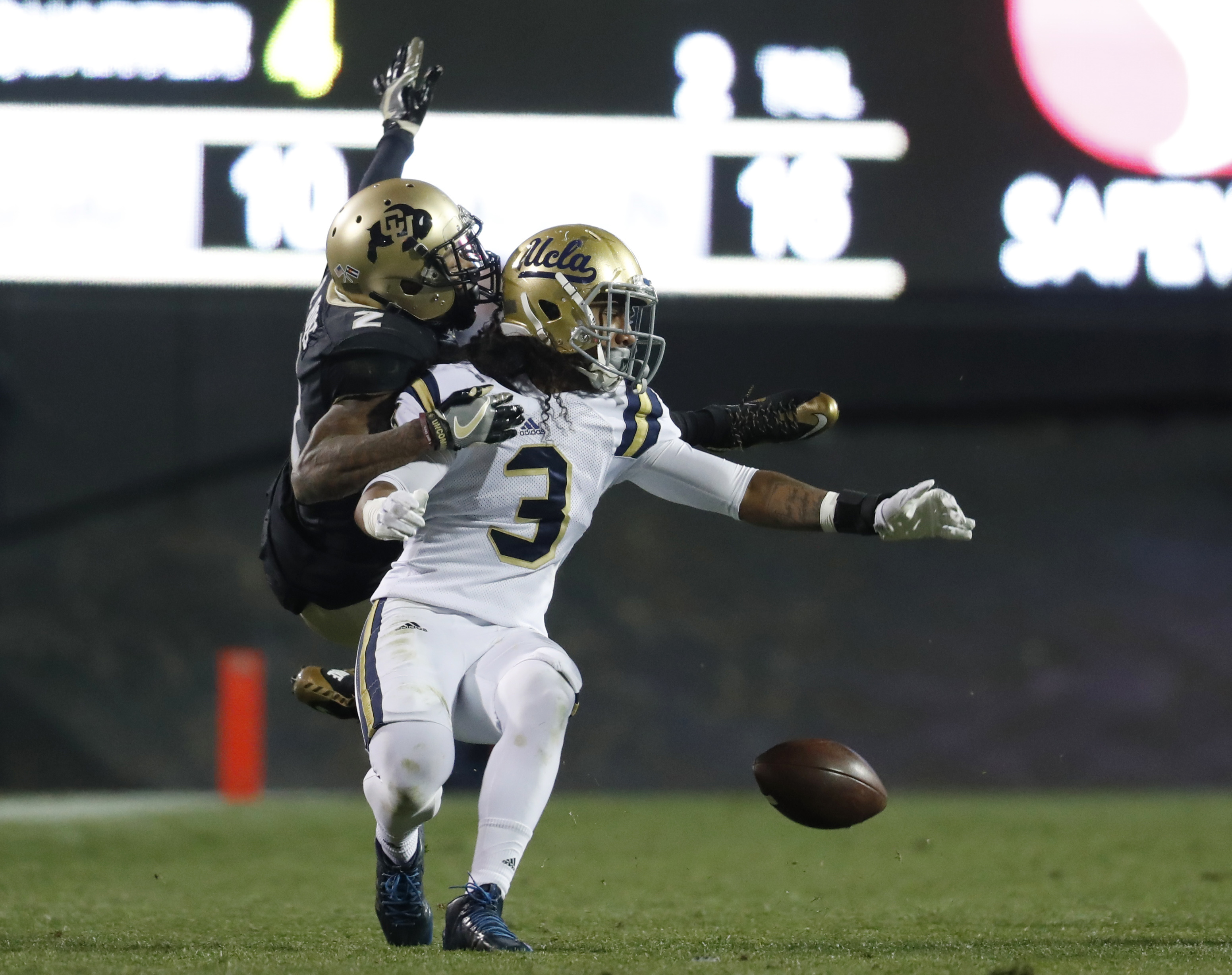 In this Thursday, Nov. 3, 2016, photo, Colorado wide receiver Devin Ross, left, pulls down UCLA defensive back Randall Goforth as he tries to intercept a pass intended for Ross in the second half of an NCAA college football game in Boulder, Colo. Colorado
