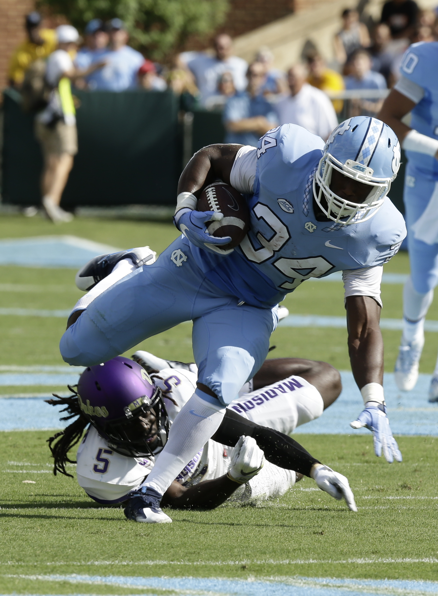 FILE - In this Sept. 17, 2016, file photo, North Carolina's Elijah Hood (34) runs past James Madison's Raven Greene (5) in the first half of an NCAA college football game in Chapel Hill, N.C. Hood has two straight 100-yard rushing performances entering Th