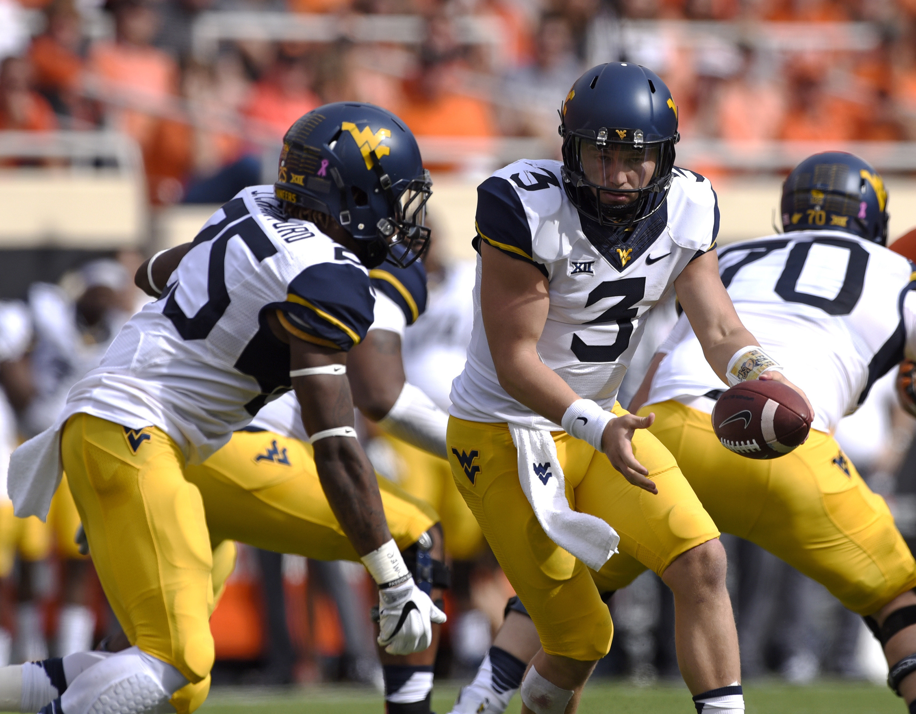 FILE - In this Oct. 29, 2016, file photo, West Virginia quarterback Skyler Howard (3) hands off to running back Justin Crawford during the team's NCAA college football game against Oklahoma State in Stillwater, Okla. West Virginia travels to play Texas th