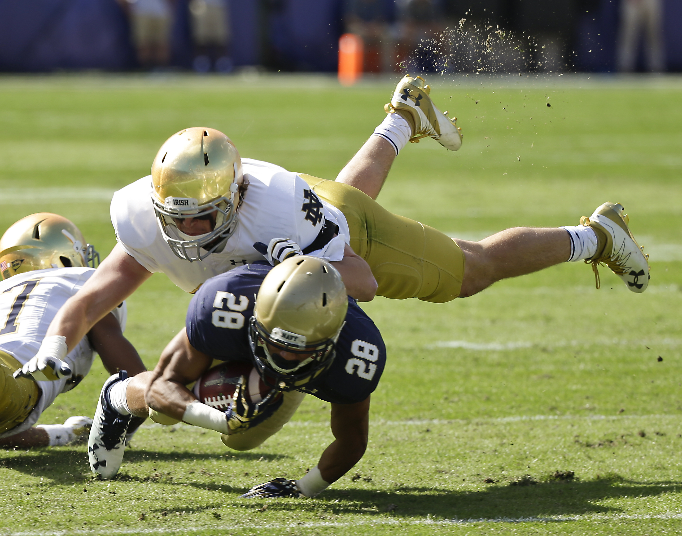 FILE - In this Nov. 5, 2016, file photo, Notre Dame linebacker Greer Martini, top, brings down Navy running back Dishan Romine (28) after a short gain during the first half of an NCAA college football game in Jacksonville, Fla. The 6-foot-3, 240-pound jun