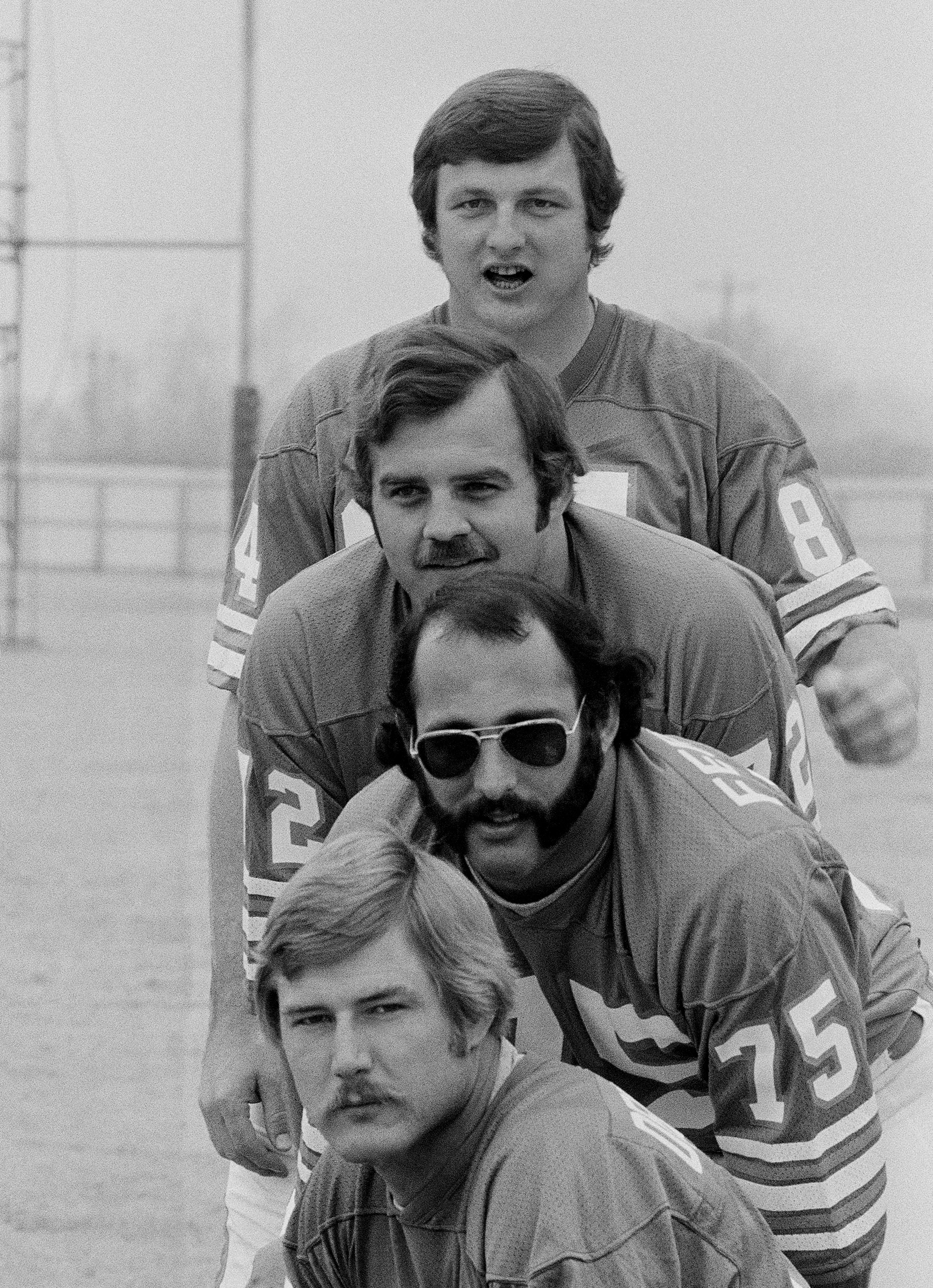 FILE - In this Jan. 7, 1974, file photo, Miami Dolphins defensive linemen, from top to bottom, Bill Stanfill, Bob Heinz, Manny Fernandez and Vern Den Herder pose in Houston during the Dolphins picture day for Super Bowl VIII. Former Georgia and Miami Dolp