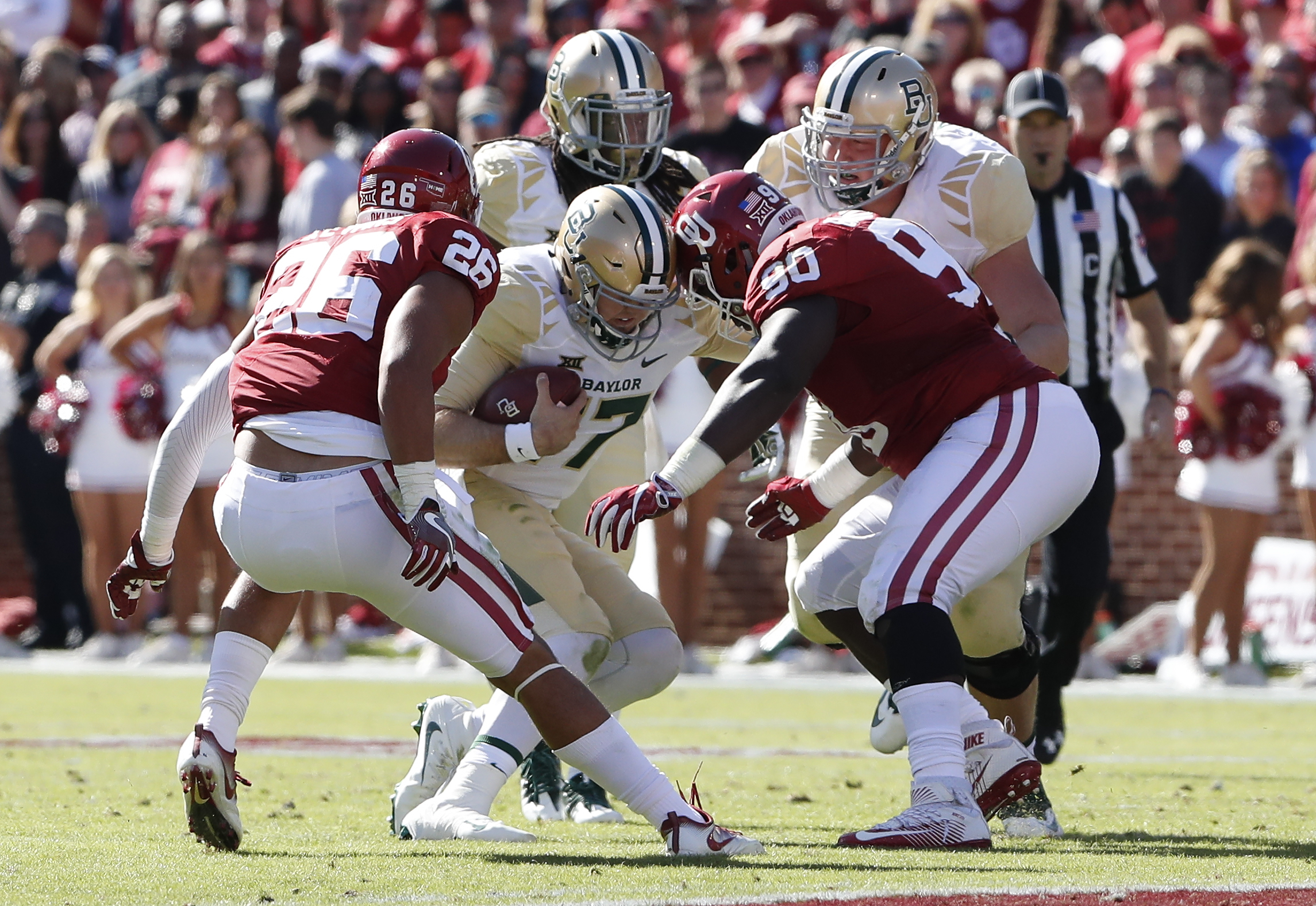 Oklahoma linebacker Jordan Evans (26) and defensive lineman Neville Gallimore (90) stop Baylor quarterback Seth Russell (17) during the first half of an NCAA college football game in Norman, Okla. on Saturday, Nov. 12, 2016. (AP Photo/Alonzo Adams)