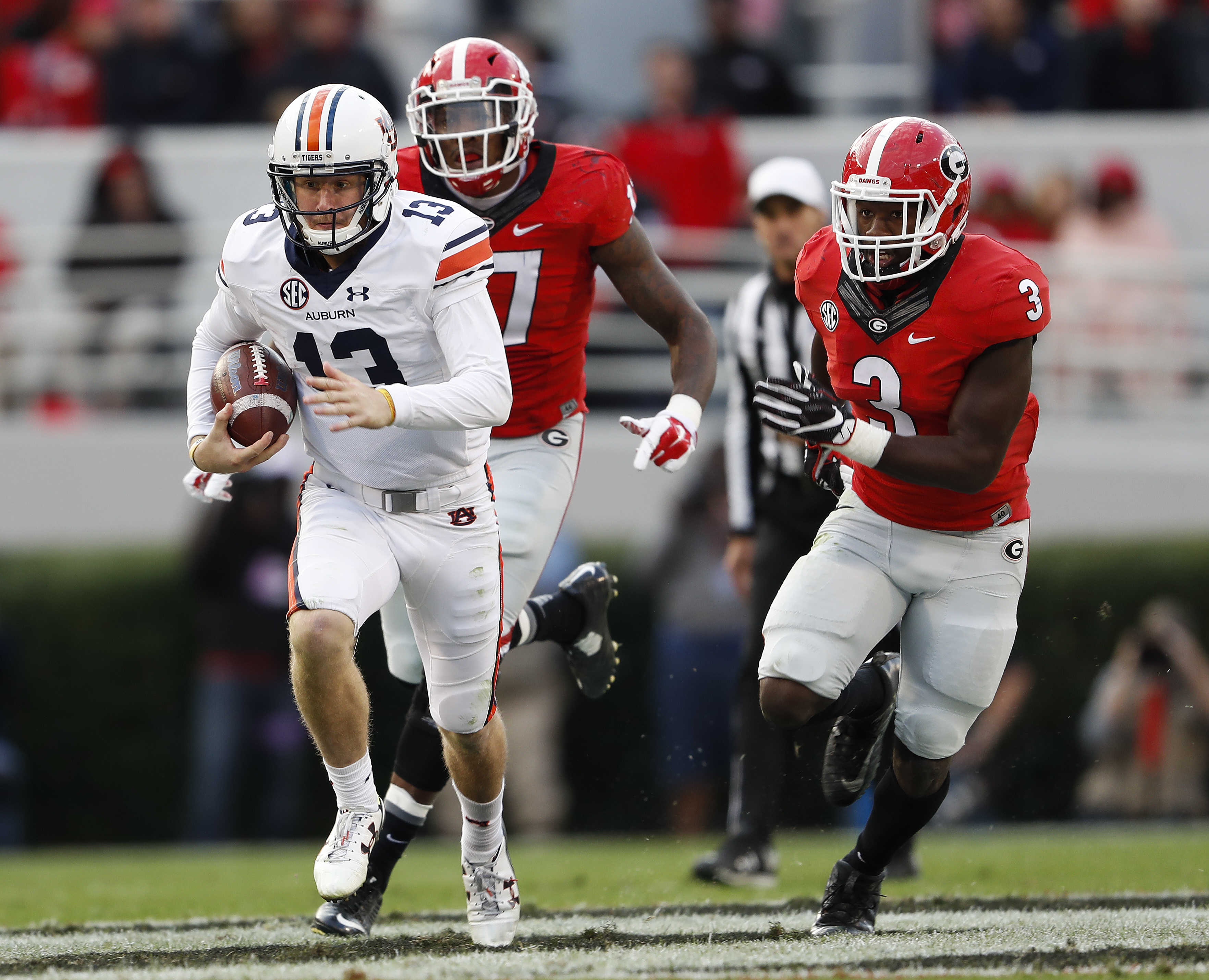Auburn quarterback Sean White (13) breaks away fro Georgia linebackers Davin Bellamy (17) and Roquan Smith (3) in the first half of an NCAA college football game Saturday, Nov. 12, 2016, in Athens, Ga. (AP Photo/John Bazemore)