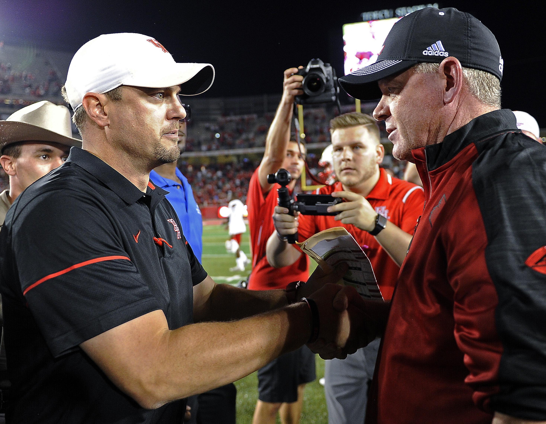 Houston coach Tom Herman, left, and Louisville coach Bobby Petrino speak following anp NCAA college football game, Thursday, Nov. 17, 2016, in Houston. Houston won 36-10. (AP Photo/Eric Christian Smith)