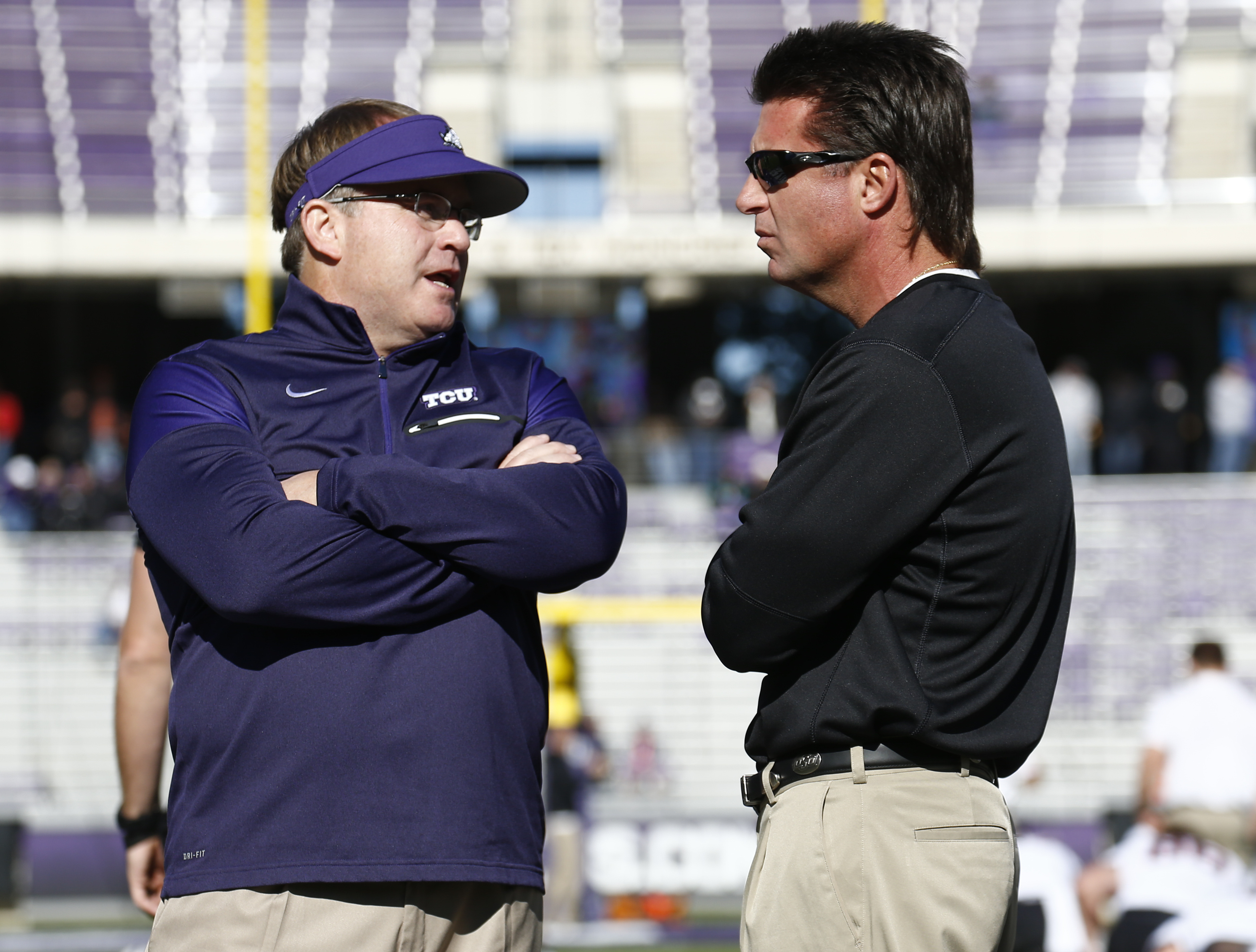 TCU head coach Gary Patterson and Oklahoma State head coach Mike Gundy talk before an NCAA college football game, Saturday, Nov. 19, 2016, in Fort Worth, Texas. (AP Photo/Jim Cowsert)
