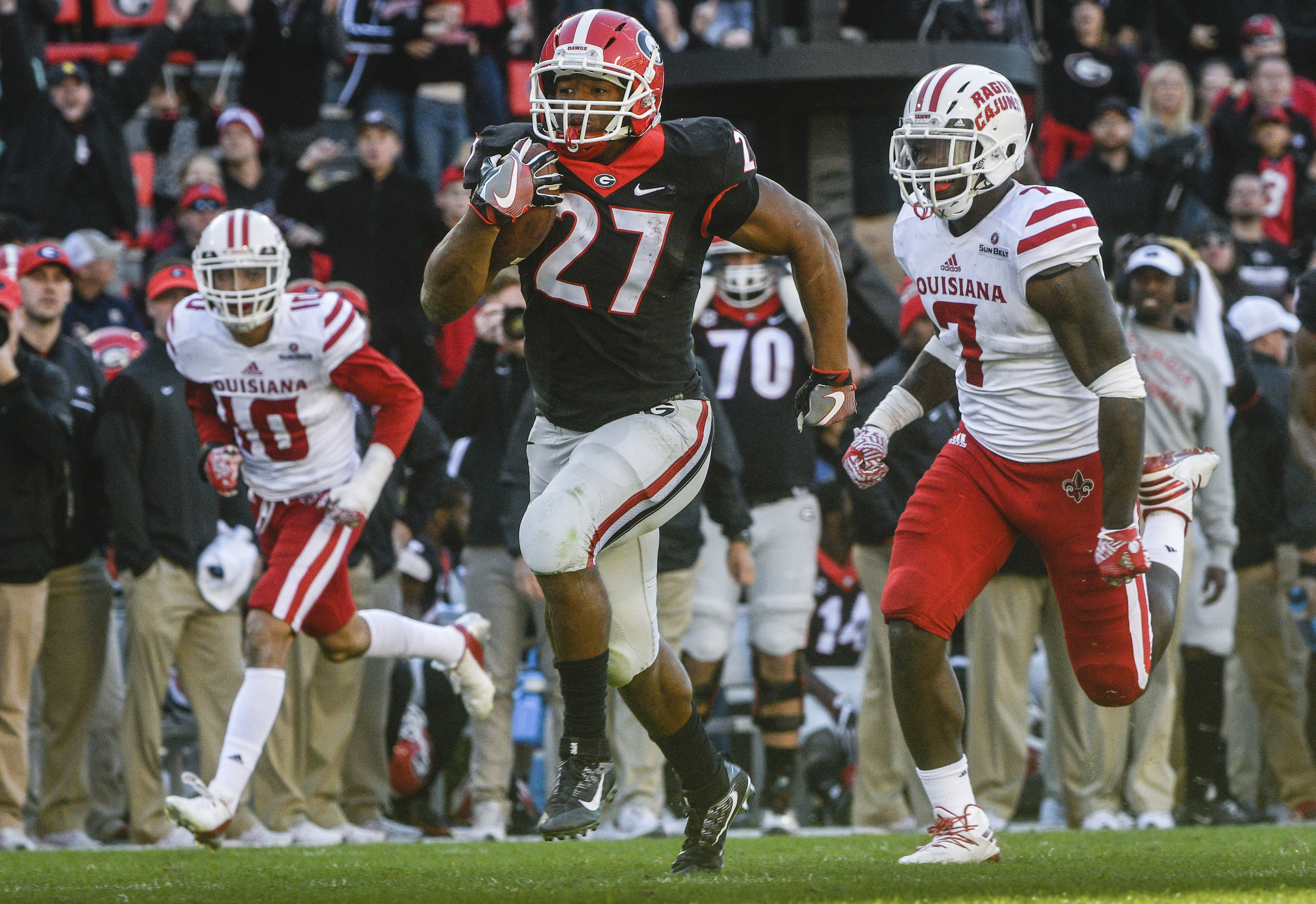 Georgia running back Nick Chubb (27) breaks ahead from the defense of Louisiana Lafayette linebacker Otha Peters (7) and defensive back Christian Goodlett (10) on a long touchdown run during the fourth quarter of an NCAA college football game, Saturday, N