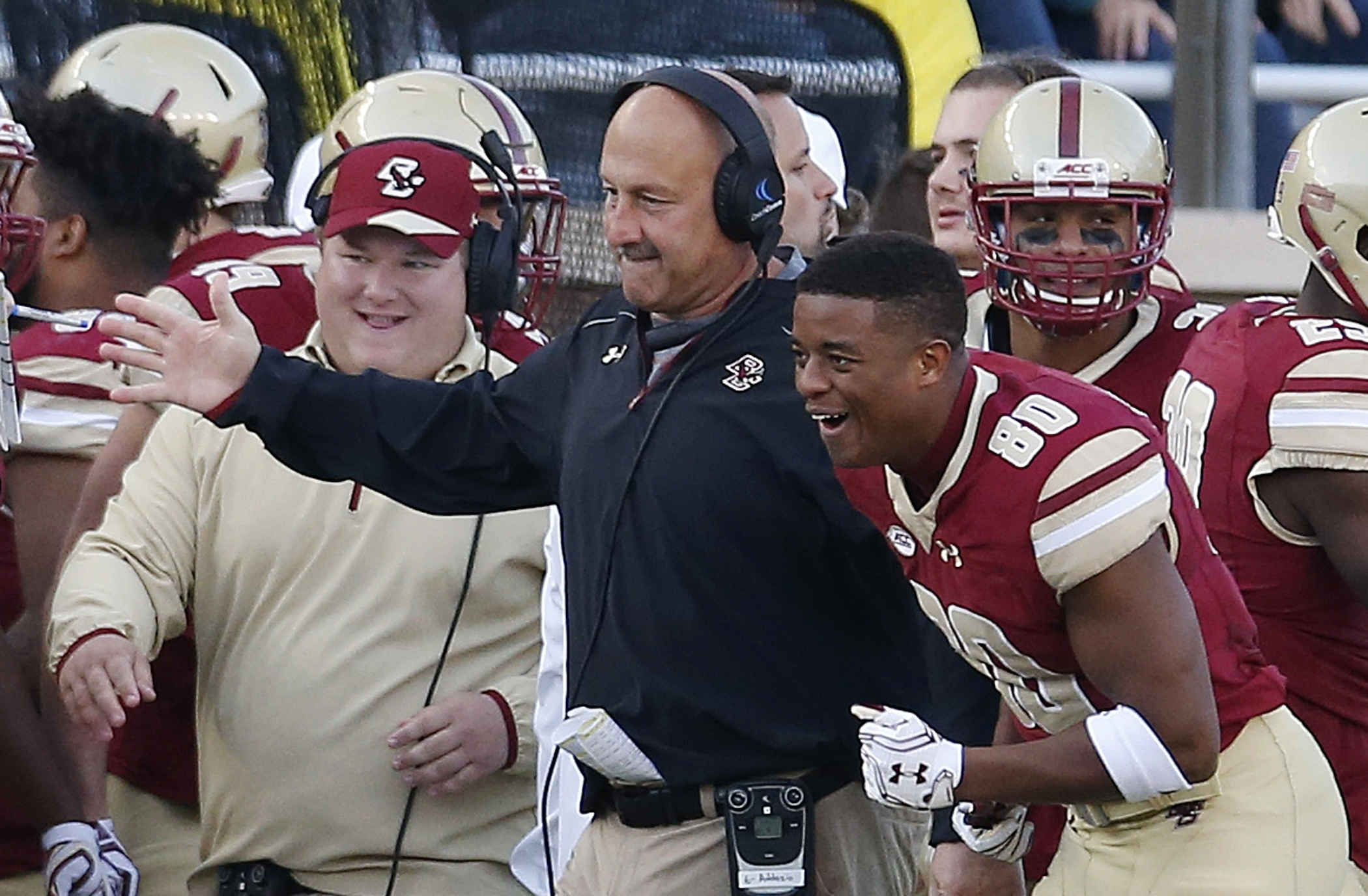 Boston College head coach Steve Addazio, center, celebrates with wide receiver Drew Barksdale (80) after a touchdown interception during the second half of an NCAA college football game against Connecticut in Boston, Saturday, Nov. 19, 2016. Boston Colleg