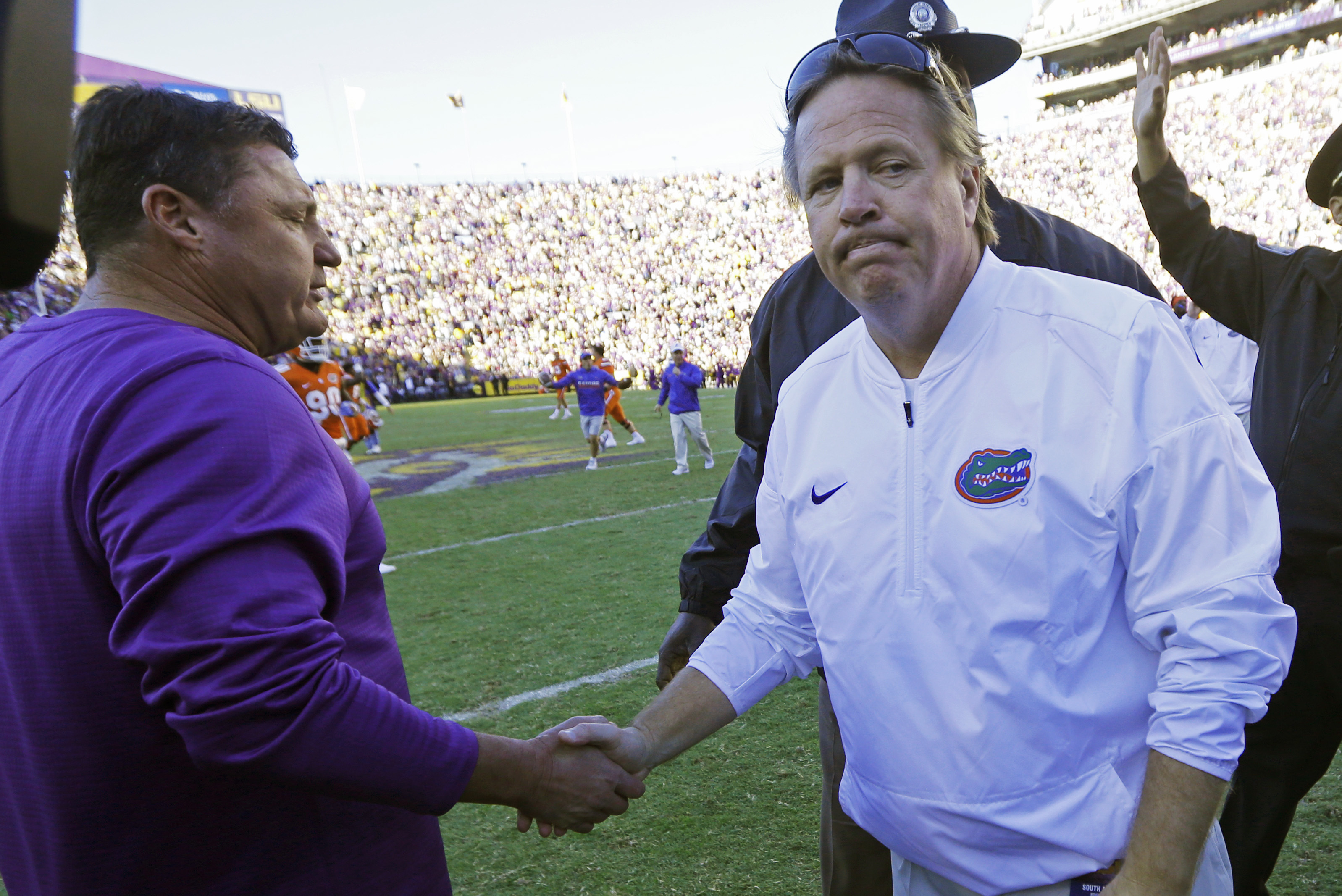 LSU interim head coach Ed Orgeron, left, and Florida head coach Jim McElwain greet each other after an NCAA college football game in Baton Rouge, La., Saturday, Nov. 19, 2016. Florida won 16-10. (AP Photo/Gerald Herbert)