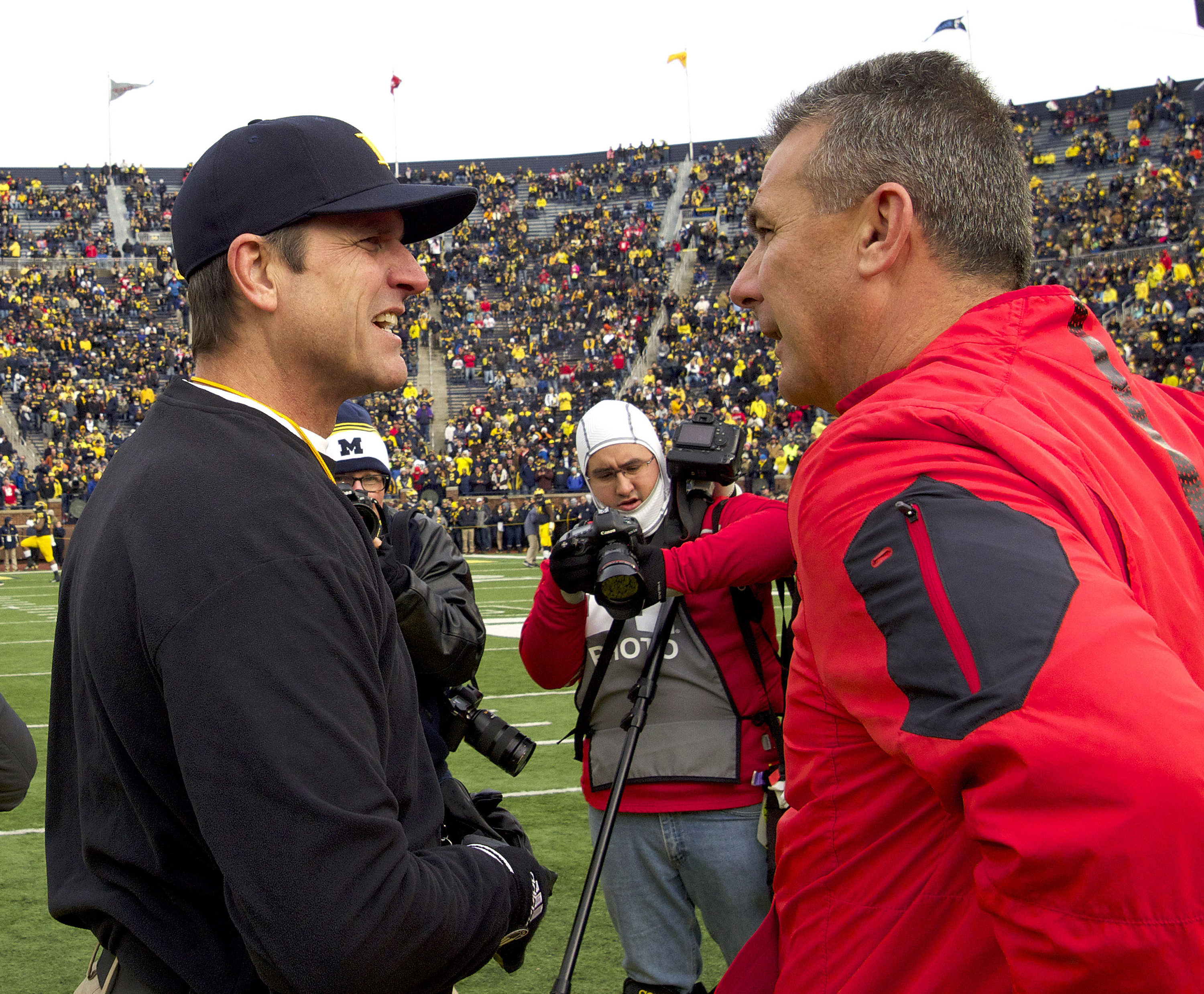 FILE - In this Nov. 28, 2015, file photo, Michigan head coach Jim Harbaugh, left, greets Ohio State head coach Urban Meyer on the Michigan Stadium field before an NCAA college football game in Ann Arbor, Mich. Harbaugh hopes to help Michigan upset Ohio St