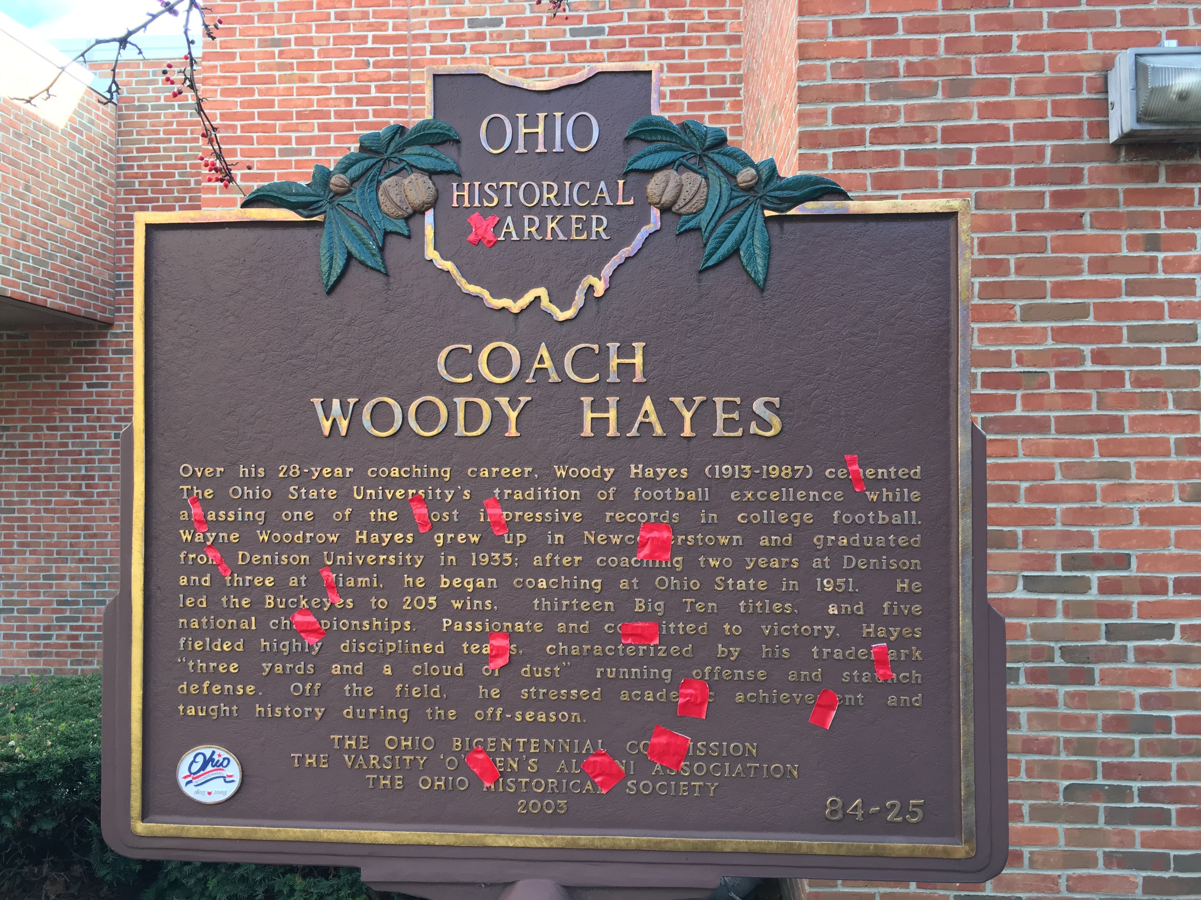 Red tape covers the Ms on the official state Ohio historical marker recognizing former Ohio State NCAA college football coach Woody Hayes at the Woody Hayes Football Center on the Ohio State University campus in Columbus, Ohio,  Monday, Nov. 21, 2016. Ohi