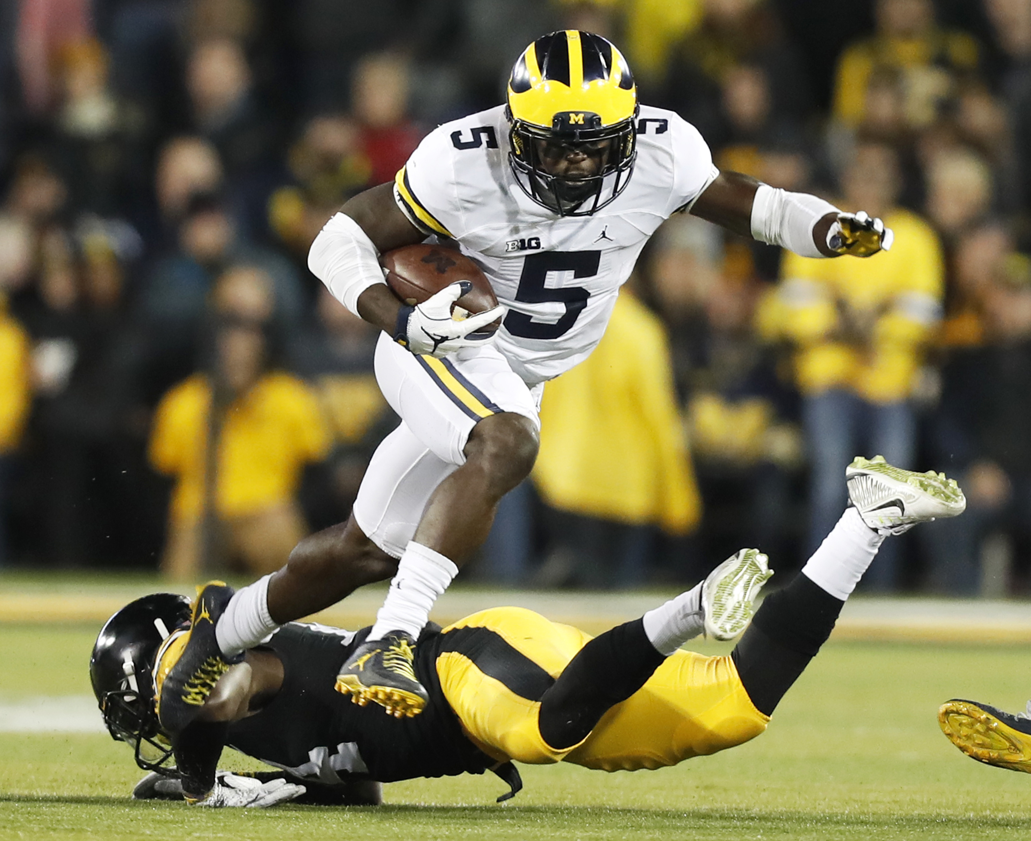 FILE - In this Nov. 12, 2016, file photo, Michigan's Jabrill Peppers (5) breaks a tackle by Iowa defensive back Desmond King, rear, during the first half of an NCAA college football game, in Iowa City, Iowa. To upset No. 2 Ohio State and win at the Horses