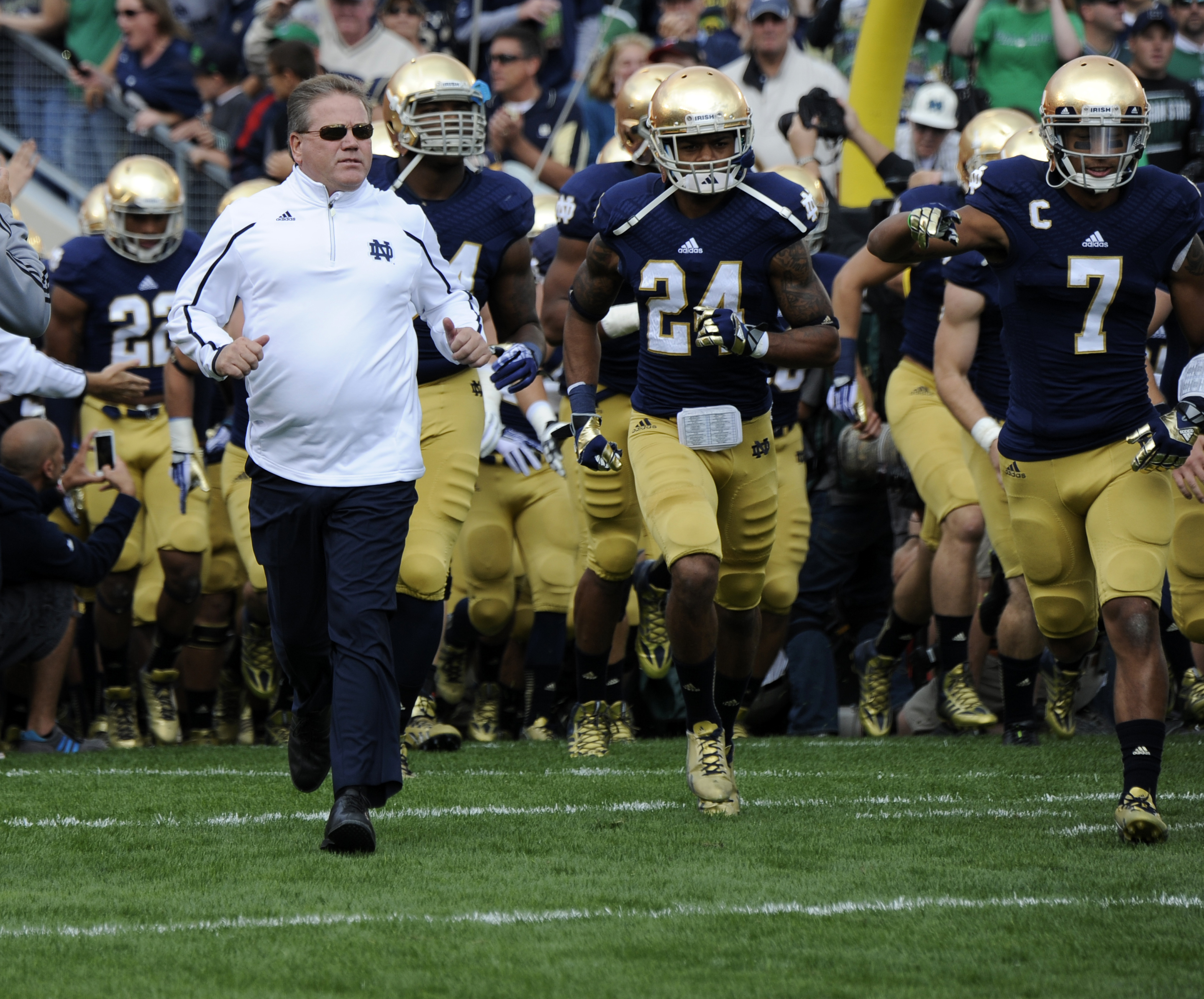 FILE - In this Sept. 21, 2013, file photo, Notre Dame coach Brian Kelly runs onto the field with his team prior to a in a NCAA college football game with Michigan State in South Bend, Ind. The NCAA is ordering Notre Dame to vacate wins from its 2012 and 2
