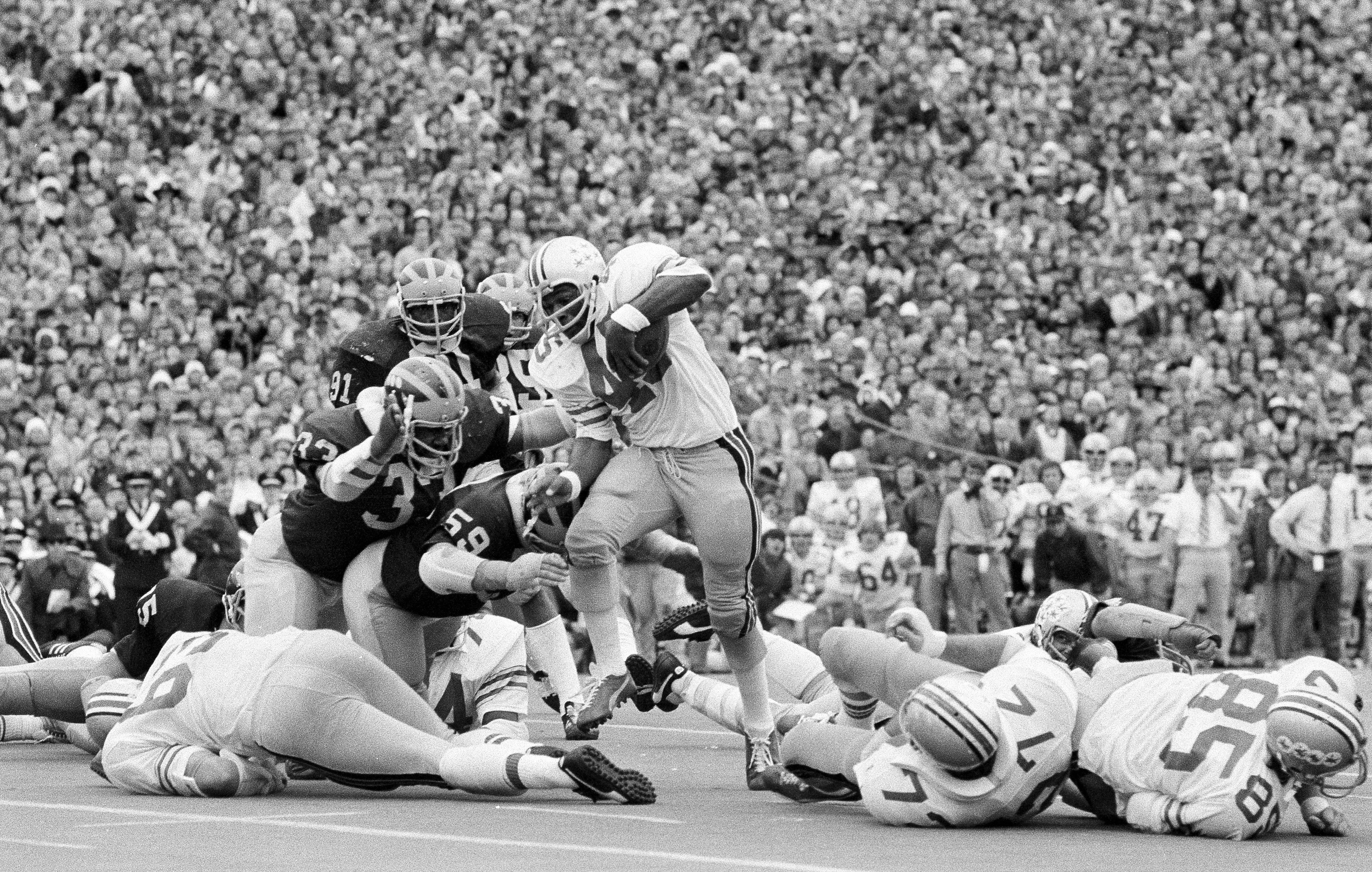 FILE - In this Nov. 24, 1973, file photo, Ohio State's Archie Griffin picks up some of his game-high 163 yards against Michigan during an NCAA college football game in Ann Arbor, Mich., as Michigan's Walt Williamson (91), Carl Russ (33) and Steve Strinko