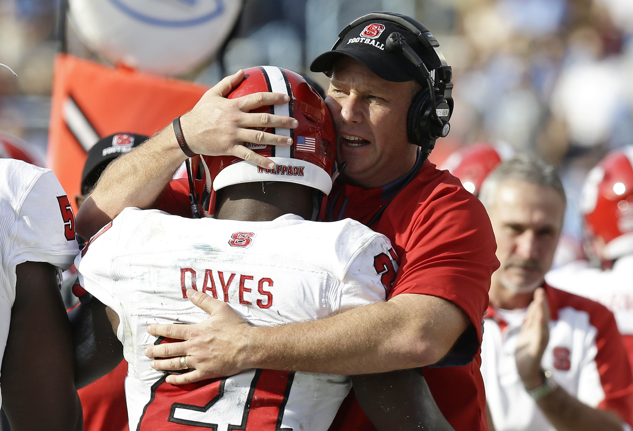 North Carolina State coach Dave Doeren hugs Matthew Dayes (21) following Dayes' touchdown against North Carolina during the first half of an NCAA college football game in Chapel Hill, N.C., Friday, Nov. 25, 2016. North Carolina won 28-21. (AP Photo/Gerry