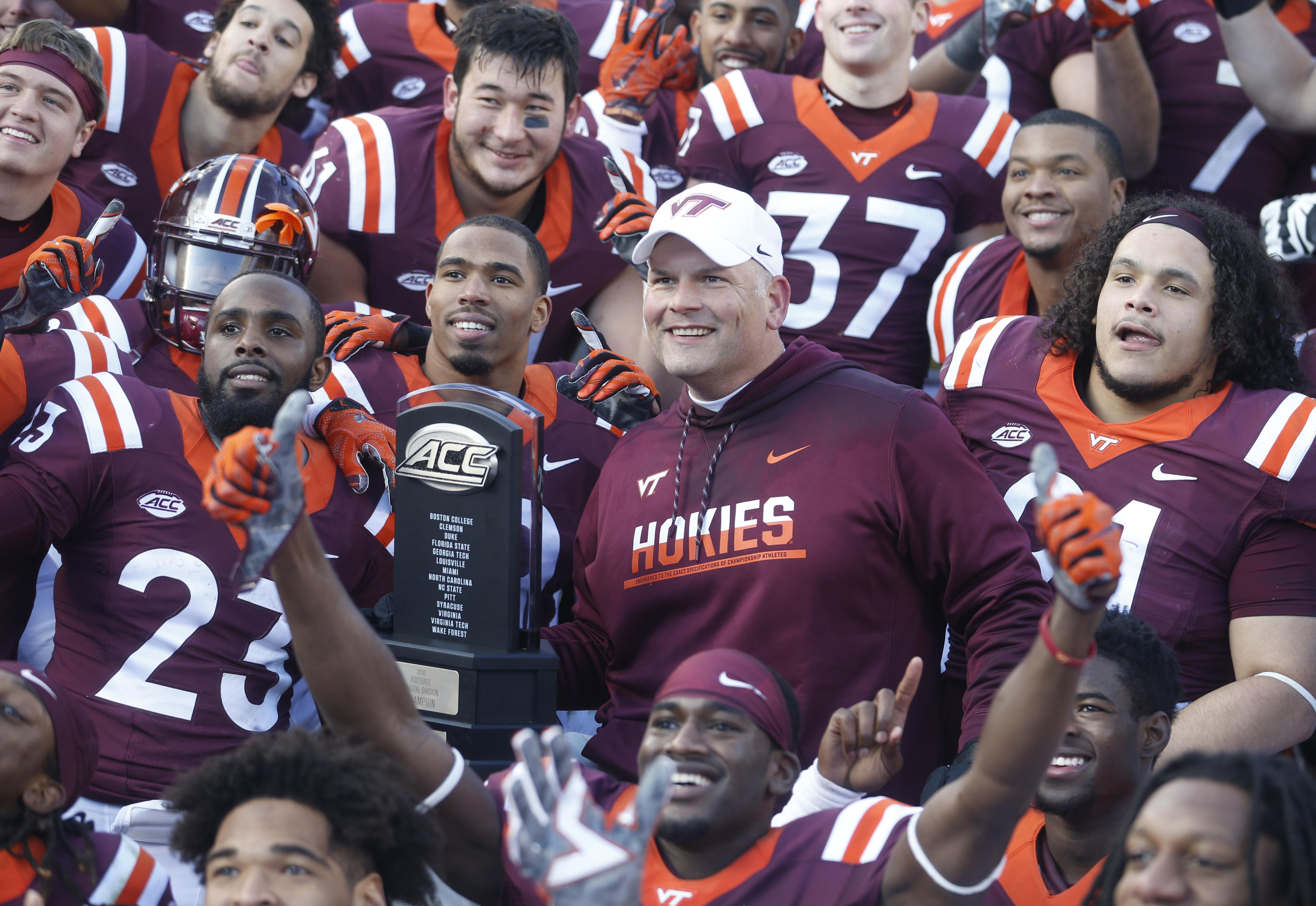 Virginia Tech head coach Justin Fuente and his team celebrate their 52-10 win over Virginia after an NCAA college football game in Blacksburg, Va., Saturday, Nov. 26, 2016. (AP Photo/Steve Helber)